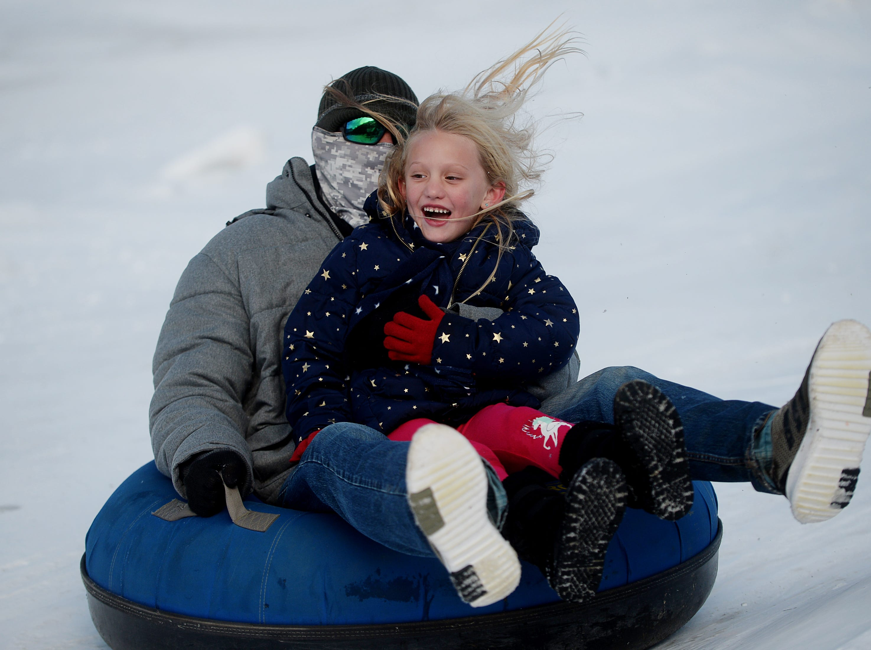 Kinley James slides down the hill at the Zip N Slip Snow Tubing Park in Mars Hill with her father, Gary, on Dec. 22, 2018. It was the first time the 5-year-old, of Sarasota, Florida, had seen snow.