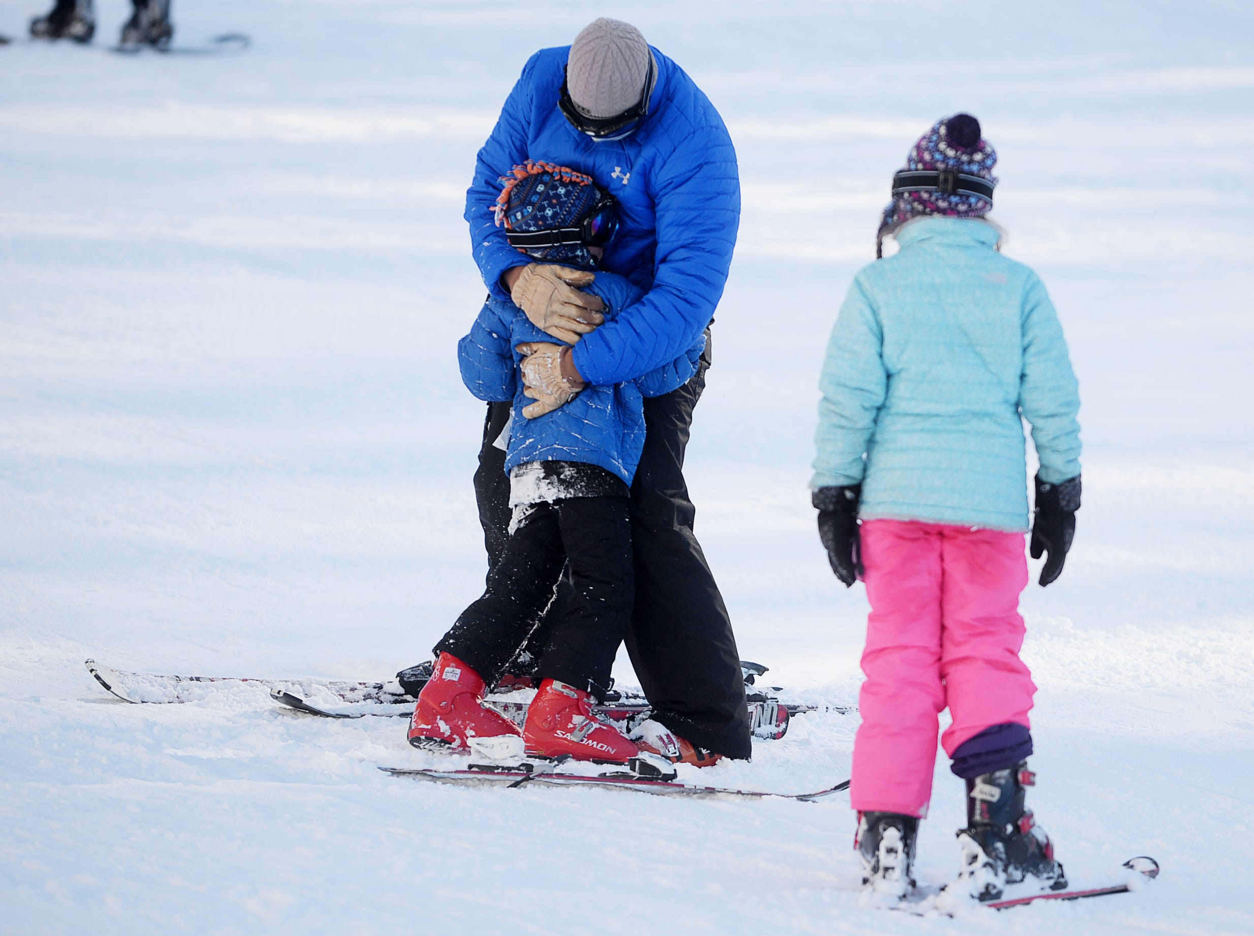 Justin Ruzicka consoles his son, Logan, after the 7-year-old fell while skiing at Wolf Ridge Ski Resort as his daughter, Amelia, 9, looks on in Mars Hill Dec. 22, 2018.