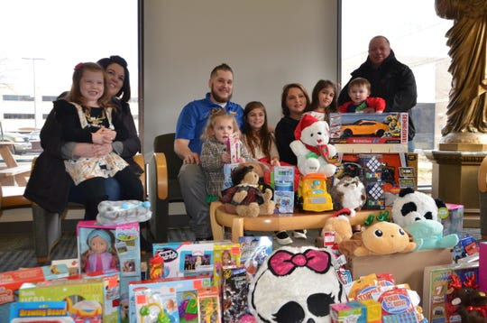 Hazel Chaltraw (center) poses with family members in front of toys collected from a toy drive she started for hospitalized children at Bronson Battle Creek.