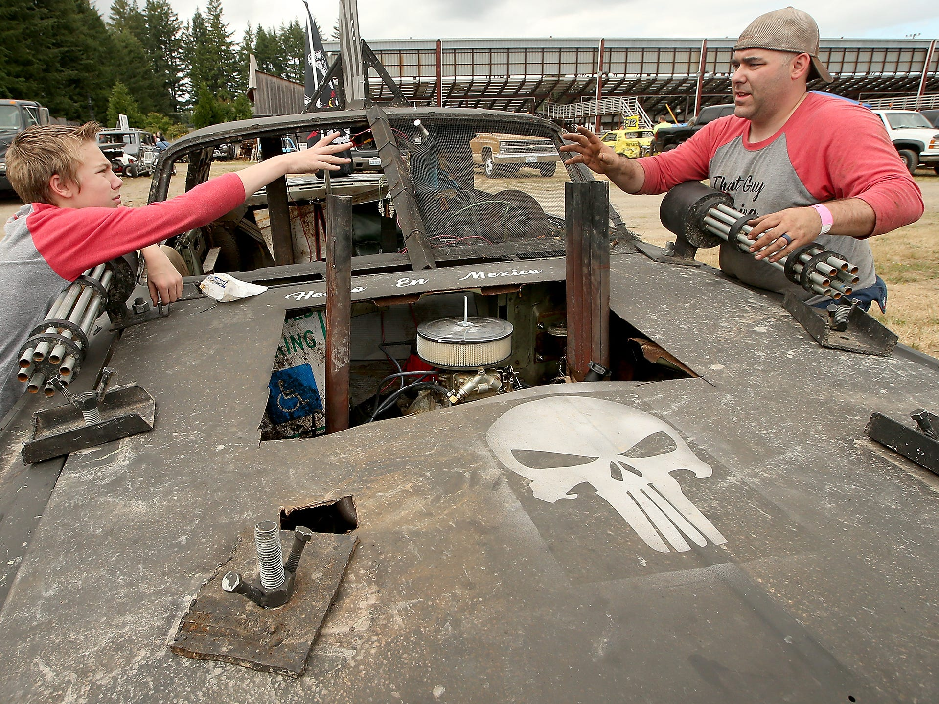 Pitman Zachary Lewis, 14, tosses a screw to his father Kevin as they attach the machine gun replicas to the hood of Kevin's car prior to the start of the Kitsap Destruction Derby at Thunderbird Stadium in Bremerton, Washington on Saturday, June 23, 2018.