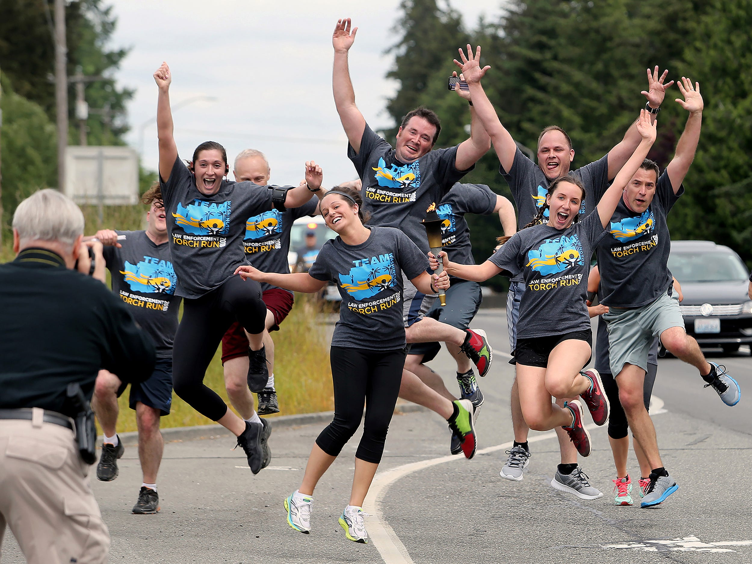 The Kitsap County Sheriffs Office Special Olympics torch running team does a ceremonial leap in front of Kitsap County Deputy Scott Wilson at the end of their running leg at Highway 303 and Fairgrounds Road on Thursday May 31, 2018. Holding the torch in the center left is corrections officer Erin Swallom, and corrections nurse Bailey Montgomery.