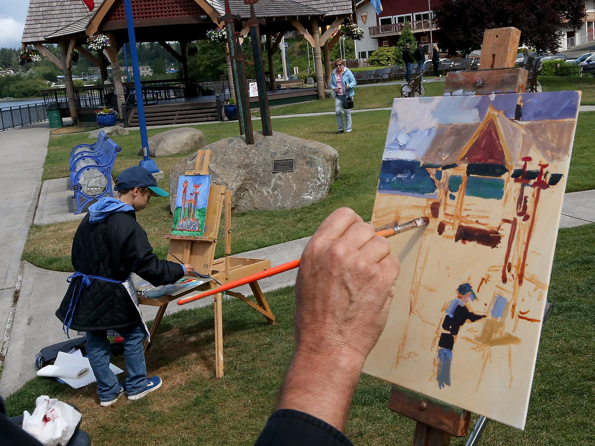 Robin Weiss, of Poulsbo, added his grandson Chase Koenigs, 8, (at left) into his painting as the two take part in the Plein Air Competition at Poulsbo's Waterfront Park on Friday, June 1, 2018. The painting competition kicked off the start of Paint out Poulsbo, a two-day music and arts festival organized by Peninsula Music and Arts Society.