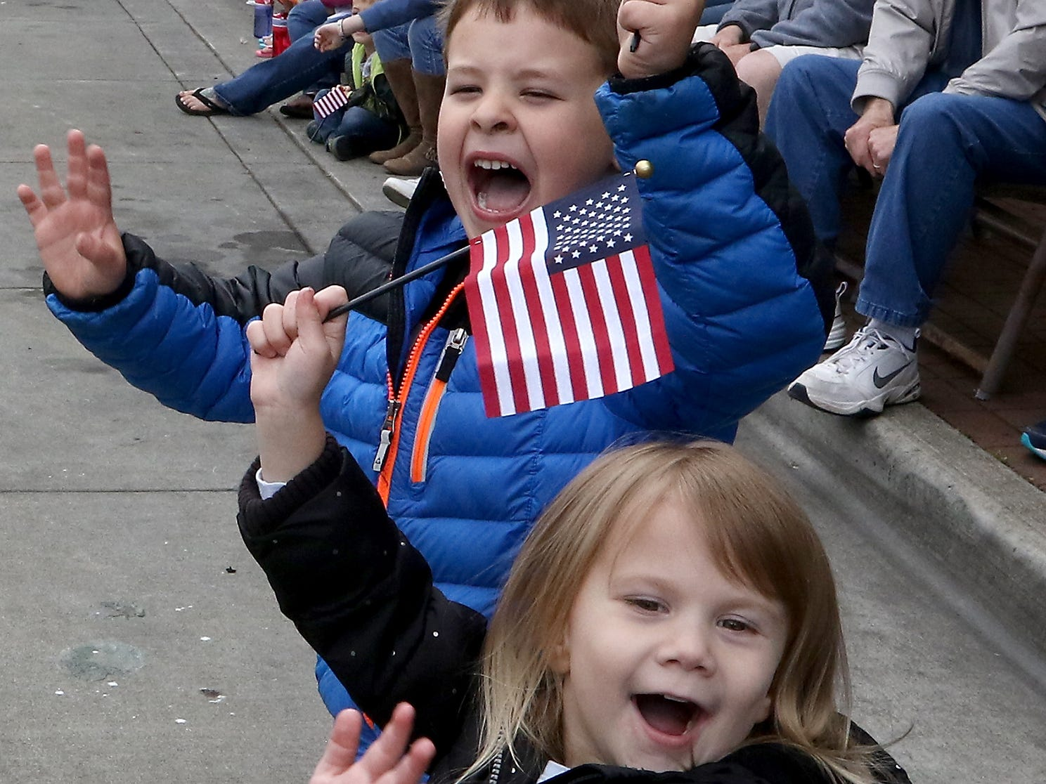 Joel Deem, 5, (back) and Aria Nordeen, 3, exuberantly wave their flags at the Bremerton Fire Department trucks passing them during the Armed Forces Day Parade in downtown Bremerton, Washington on Saturday, May 19, 2018.