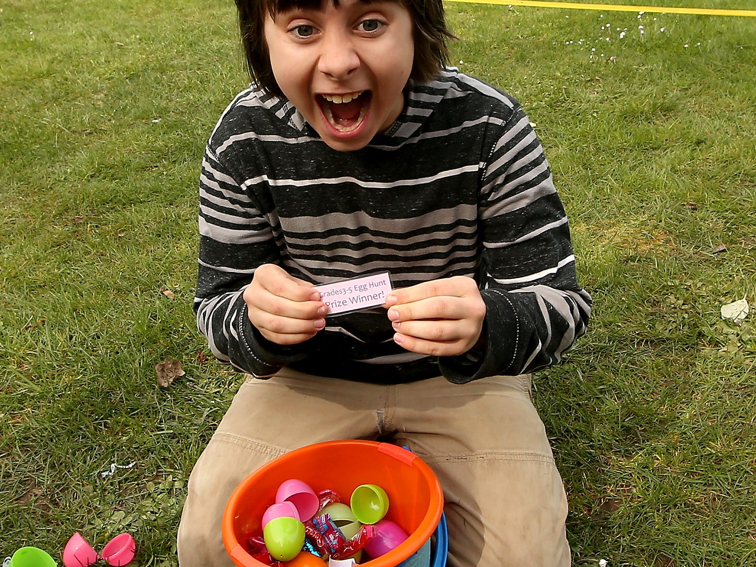 An excited Adam Champion, 10, of Bainbridge Island, reacts to the grand prize ticket that he found inside one of the plastic eggs he collected during the mEGGa Hunt at Bainbridge Island, Washington's Battle Point Park on Saturday, March 31, 2018.