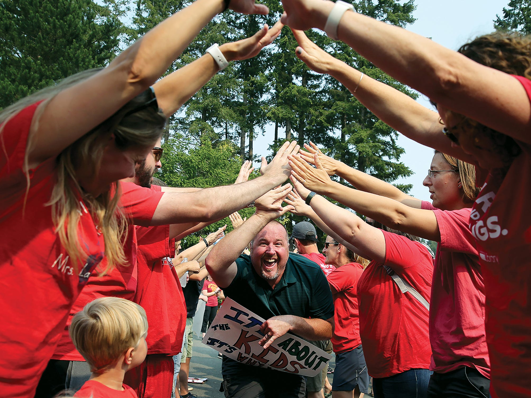 Kingston Middle School teacher Ted Jez goes through the tunnel gauntlet at the rally at the WEA headquarters in Poulsbo on Monday August, 13, 2018. Teachers in CKSD and NKSD rally as districts negotiate salary increases resulting from the McCleary decision. Bainbridge, with a 21 percent increase, got one of the highest salary bumps in the state. South Kitsap has reached a tentative agreement and negotiations are wrapping up in CK and NK. Bremerton will wrap up by the end of the month.