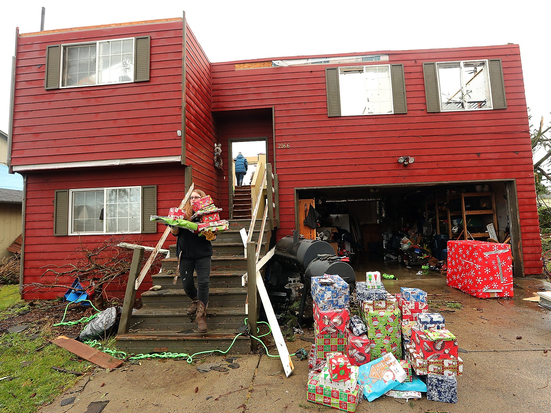 Hannah Mueller carries Christmas presents to the driveway of her parent's home as she helps salvage what they can from their now roofless structure on Tiburon Court in Port Orchard, Washington on Wednesday, December 19, 2018. A tornado touched down in the area on Tuesday.