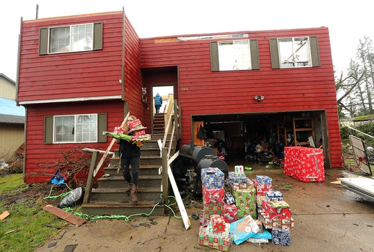 Hannah Mueller carries Christmas presents to the driveway of her parent's home as she helps salvage what they can from their now roofless structure on Tiburon Court in Port Orchard on Dec. 19, 2018.