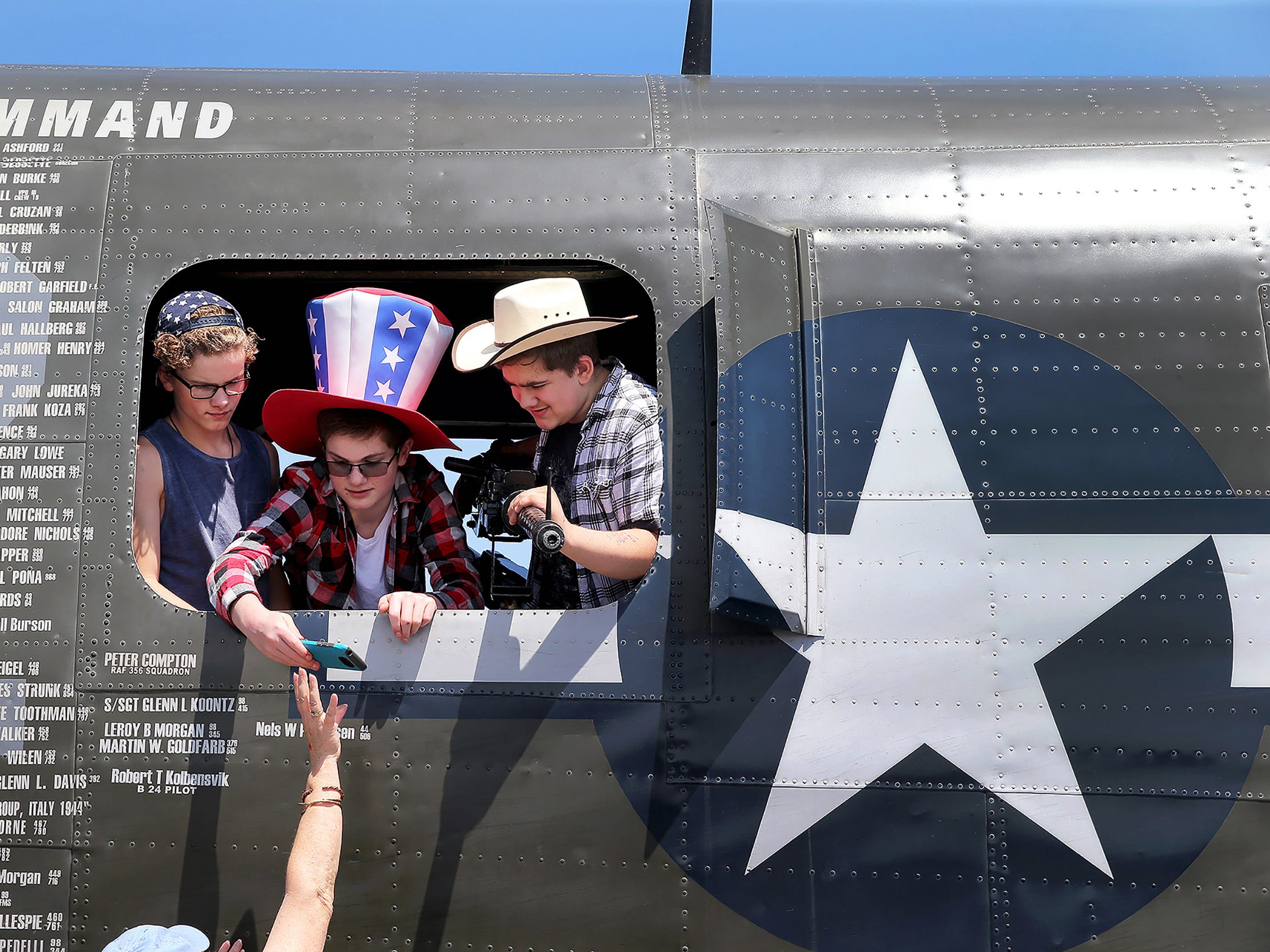 Brennan Parker, 13, center, of Gig Harbor wearing his patriotic Uncle Sam hat gets back his cell phone after getting a photo taken with his friends Logan Parrish, 13, left, of Gig Harbor, and Chris Desira, 13, right, of Lakebay. inside a Consolidated B-24 Liberator World War II aircraft at the Bremerton National Airport on Tuesday June 19, 2018. The Wings of Freedom Tour with other vintage World War II planes runs until Wednesday.