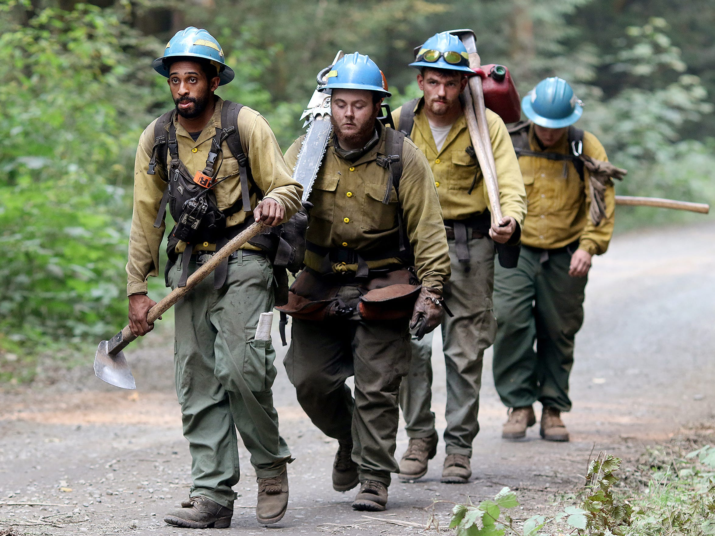Aaron Reid, front, Brendon Cunningham, Matt VanDusen, and Shane Collins from Lost River Fire Management of Klamath Falls, Oregon head back to their vehicle after working at the Maple Fire which is above the community of Hamma Hamma around 23 miles north of Shelton in the Olympic National Forest on August 15, 2018.