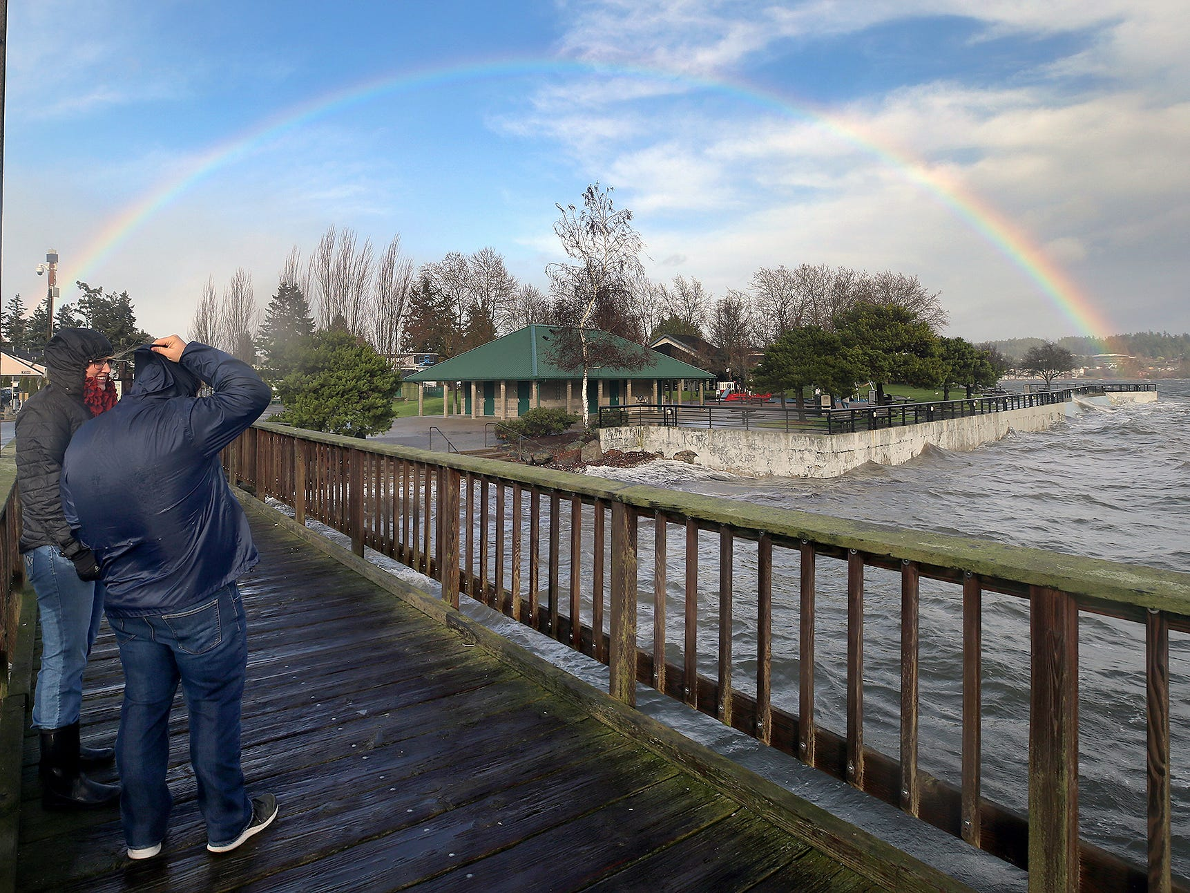 Jessica Curry, and Kyle Doth visiting during the holiday break from college have a break in the rain as a rainbow appears at Silverdale Waterfront Park Dock  on Thursday, December, 20, 2018.