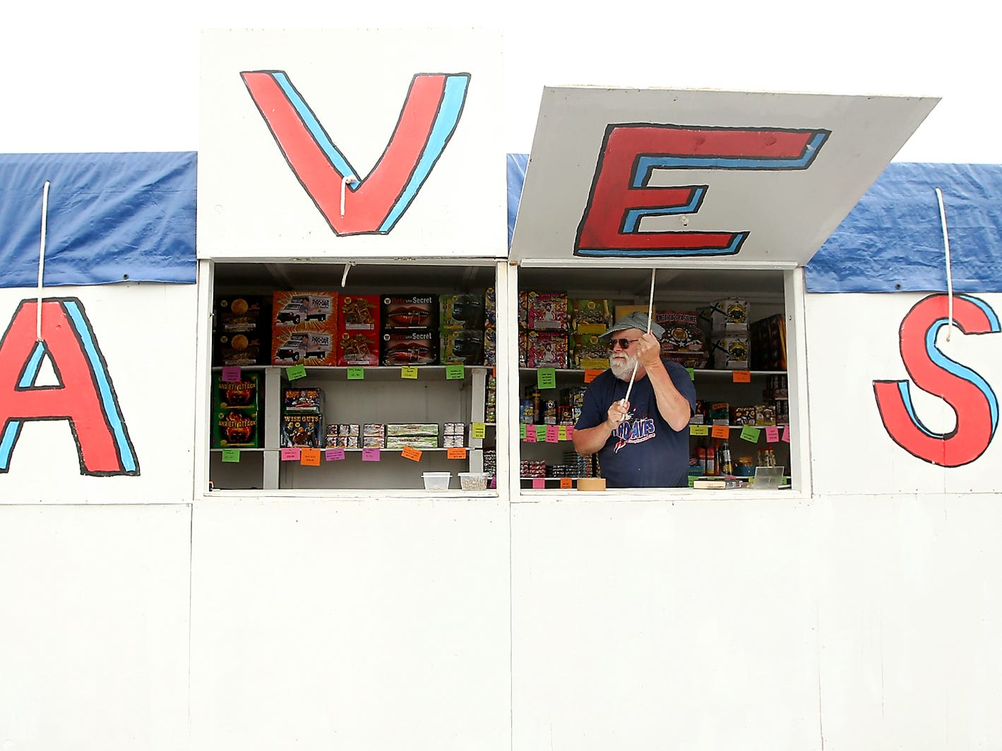 Dave Douglas hoists open one of the windows of his Pyro Dave's Fireworks stand as they ready for the first day of sales in the parking lot of Wilco in East Bremerton on Thursday, June 28, 2018. Douglas has been operating Pyro Dave's for 30 years.