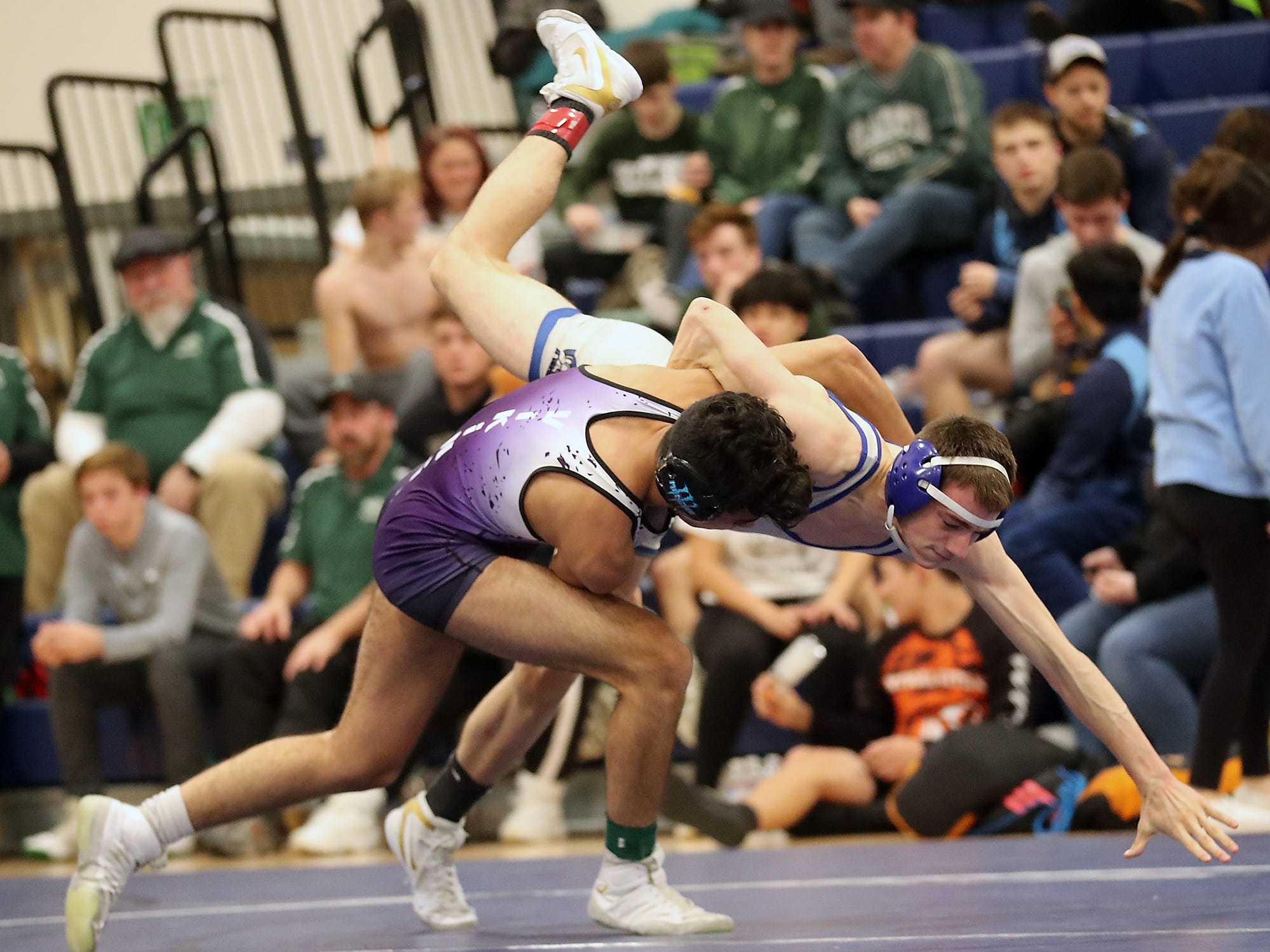 North Kitsap's Robert Gomez and Olympic's Tim Porter grapple for the first place finish in the 132-pound weight class at the North Mason Hawkins Memorial Wrestling Tournament in Belfair on Saturday, December 22, 2018.