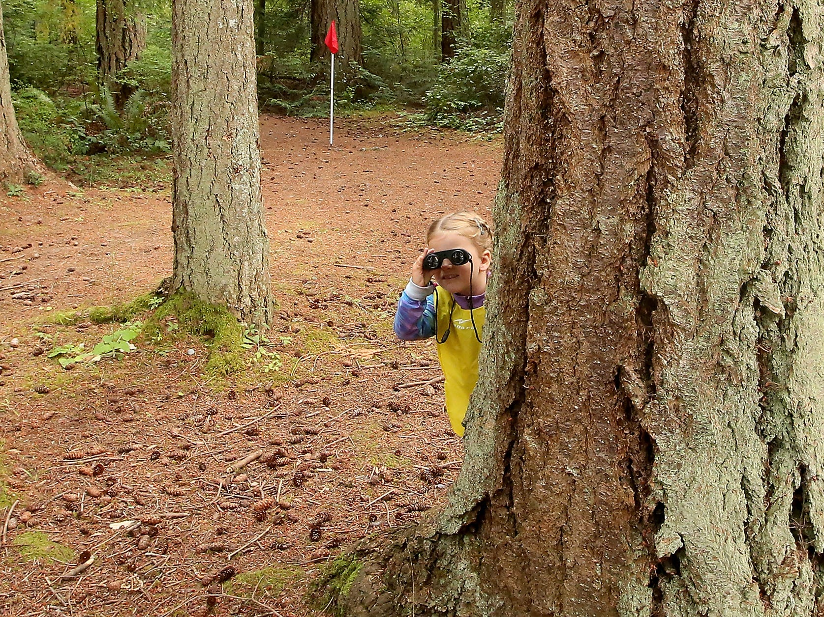 A camper hides behind a big tree and uses her binoculars during the Magnolia Forest Preschool camp at Kitsap Memorial Park in Poulsbo, Washington on Tuesday, July 10, 2018.