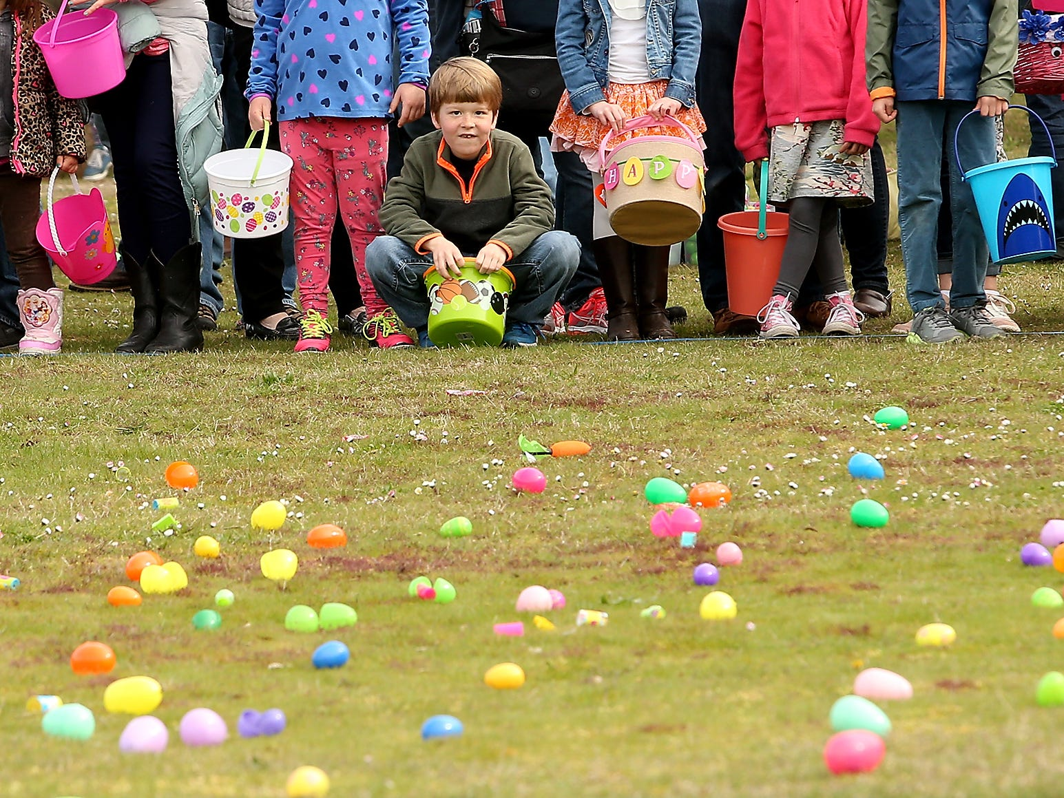 James Storm, 6, crouches down low to scope out the eggs filled with candy and prizes strewn about the grass just prior to the countdown start for the mEGGa Hunt at Battle Point Park on Bainbridge Island, Washington on Saturday, March 31, 2018.