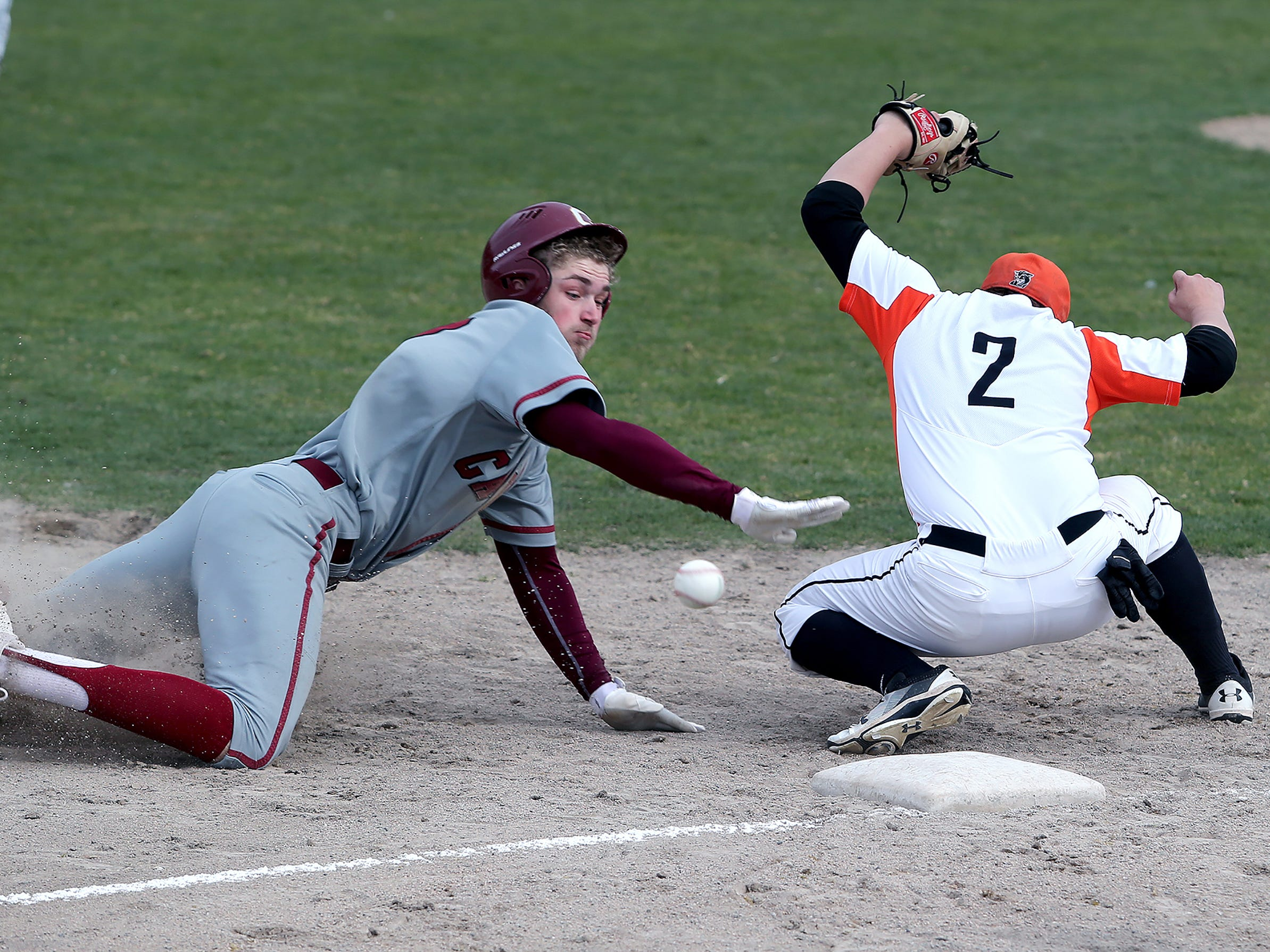 Central Kitsap third baseman Teagan Taafe can't field a throw as Capitol's Zach Burke slides in on, Tuesday April 3, 2018, at the Fairgrounds.