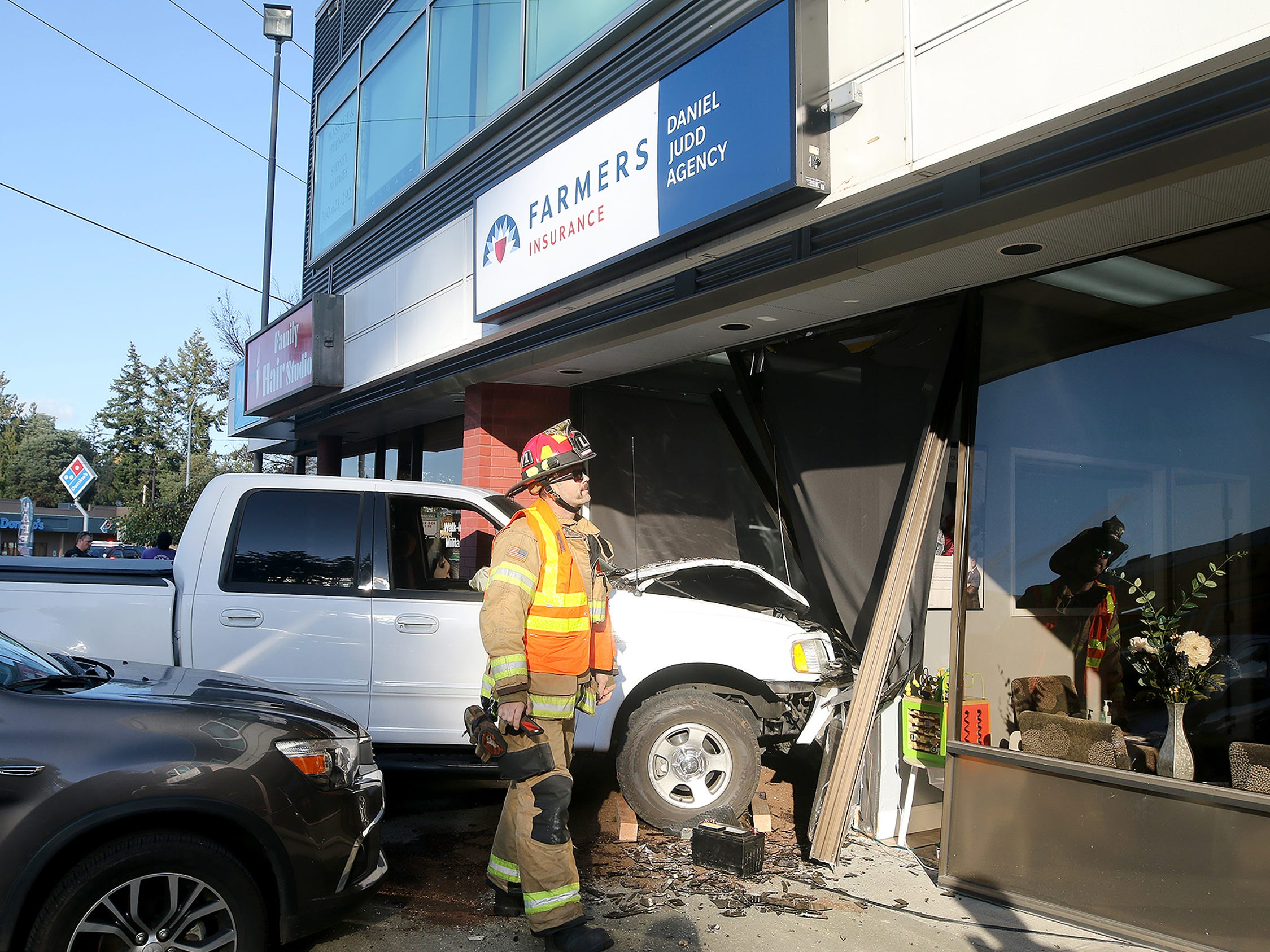 Tom Stanley of the Bremerton Fire Department inspects a building on Kitsap Way where a truck hit the front of the Farmers Insurance on Wednesday, November 7, 2018.