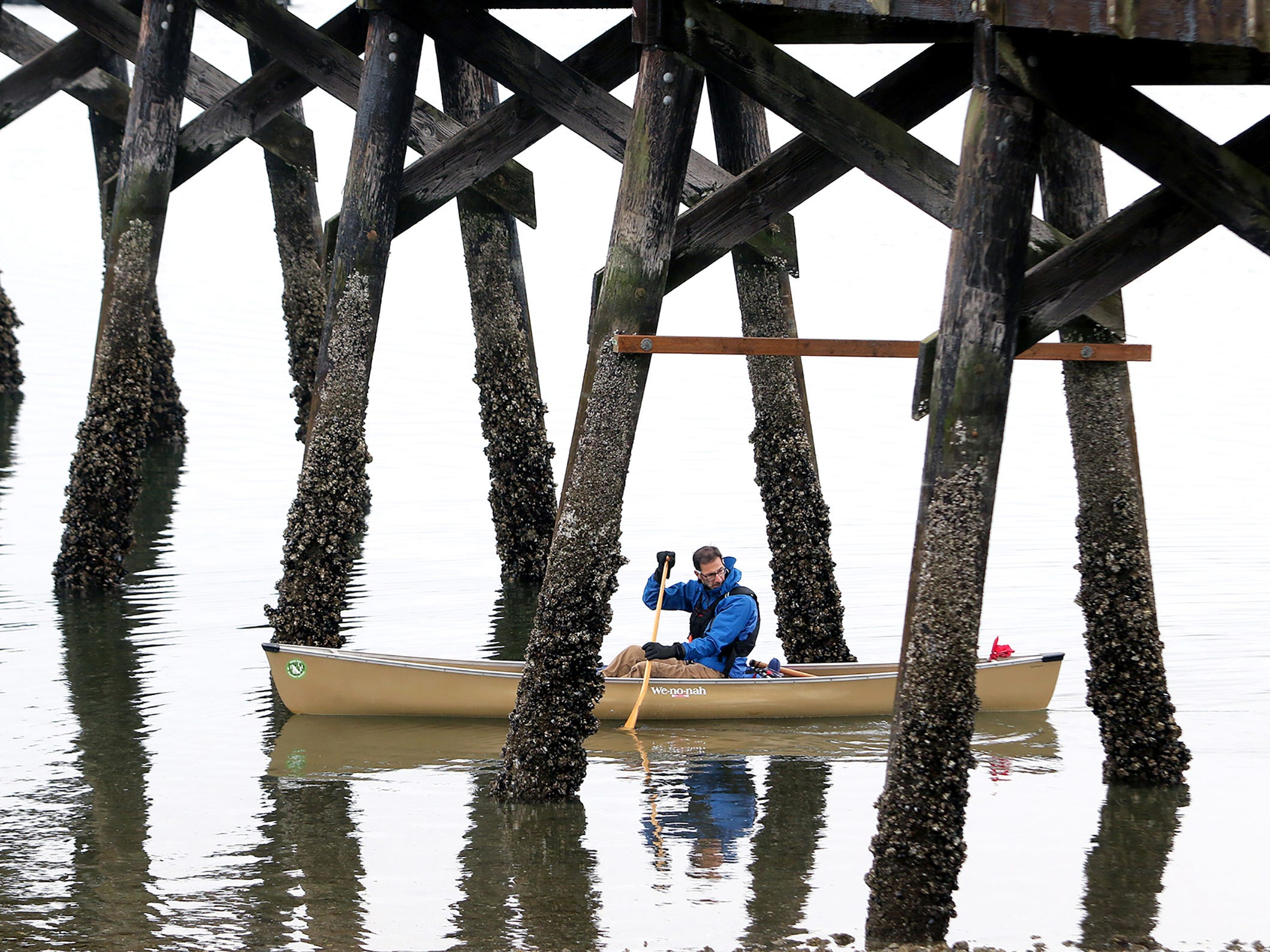 A canoeist goes under the Silverdale Waterfront Park Dock as the fog lifts on Saturday, October 20, 2018.