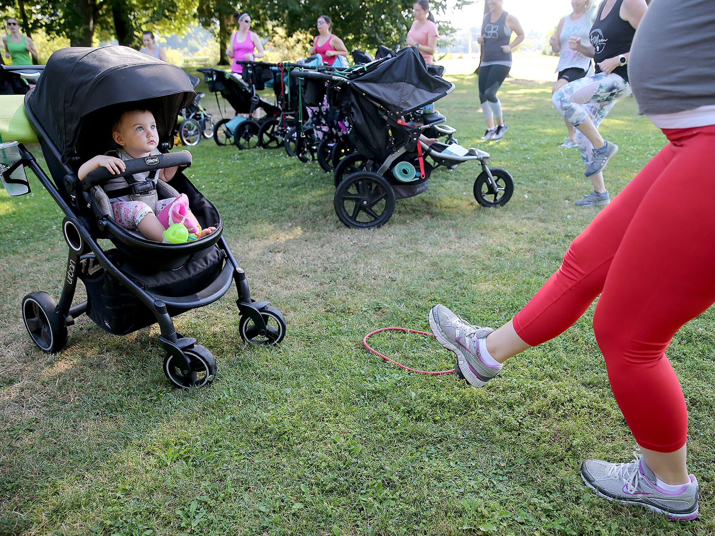 Octiva VanNostern, 18, months of Port Orchard watches as her mom Katherine works out in the Fit4Mom stroller strides exercises class for pregnant and new moms at various locations in Kitsap County. They are working out at Evergreen-Rotary Park in Bremerton on Tuesday August 7, 2018.