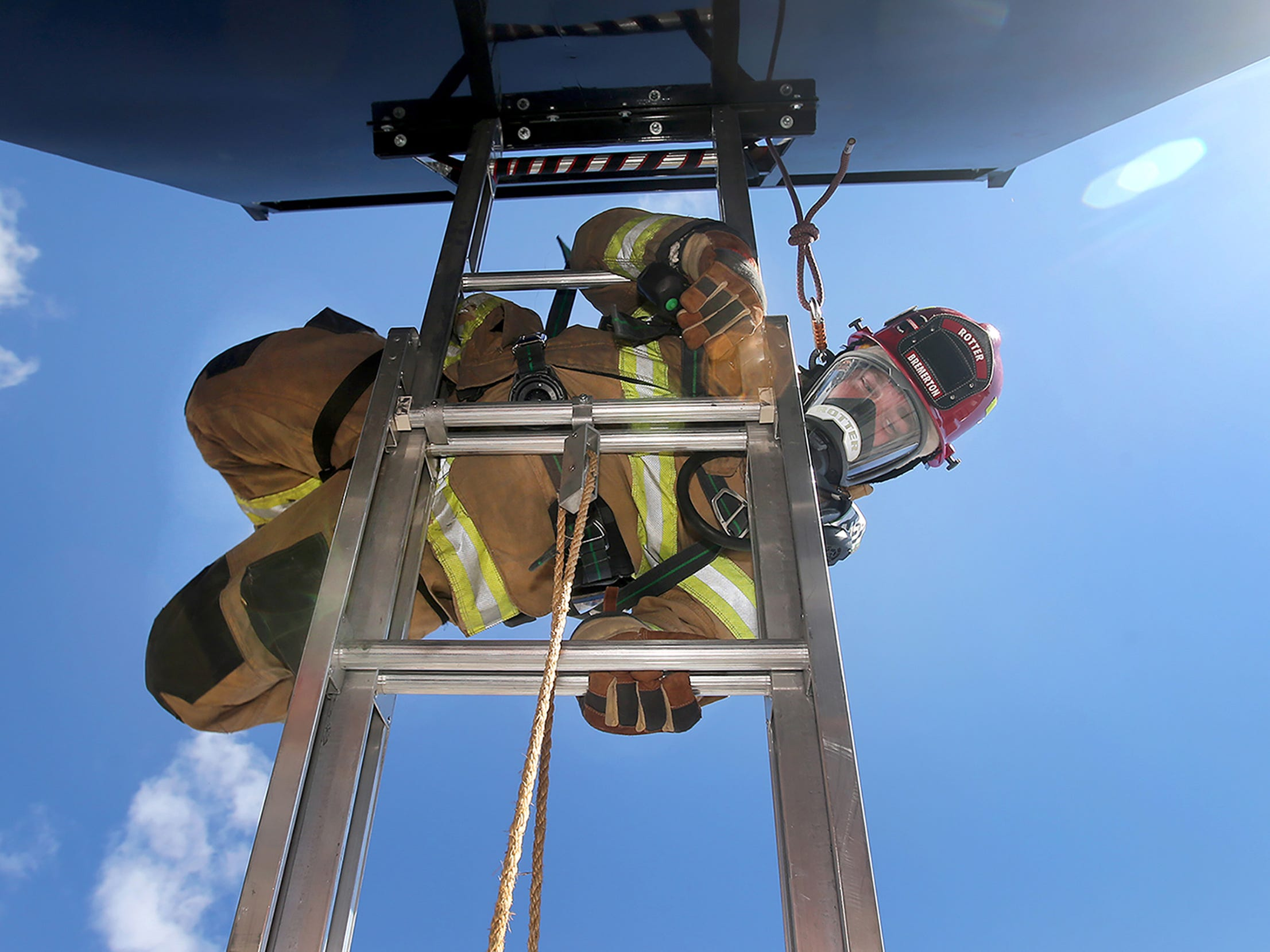 Bremerton fire Lt. Chris Rotter exits down a ladder as he practices an emergency upper floor ladder escape on Wednesday, September 19, 2018 at the Bremerton Readiness Center. The training is to teach firefighters escape routes quickly from a window.