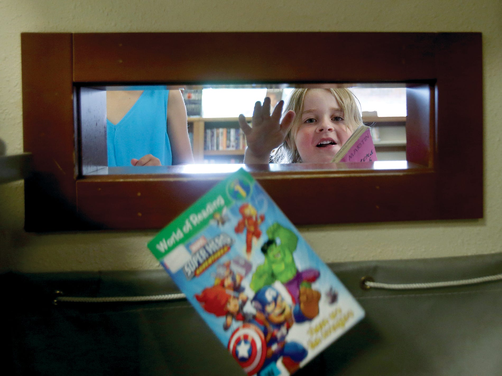 Ivan Churchman-Bailey, 4, of Bremerton drops a book into the drop box at the Kitsap Regional Library, Central Branch in East Bremerton on Tuesday. He is participating in the summer reading program to earn tickets to the Kitsap County Fair & Stampede in August. The Kitsap Regional Libraries are getting rid of the late fees as one of the levy promises.