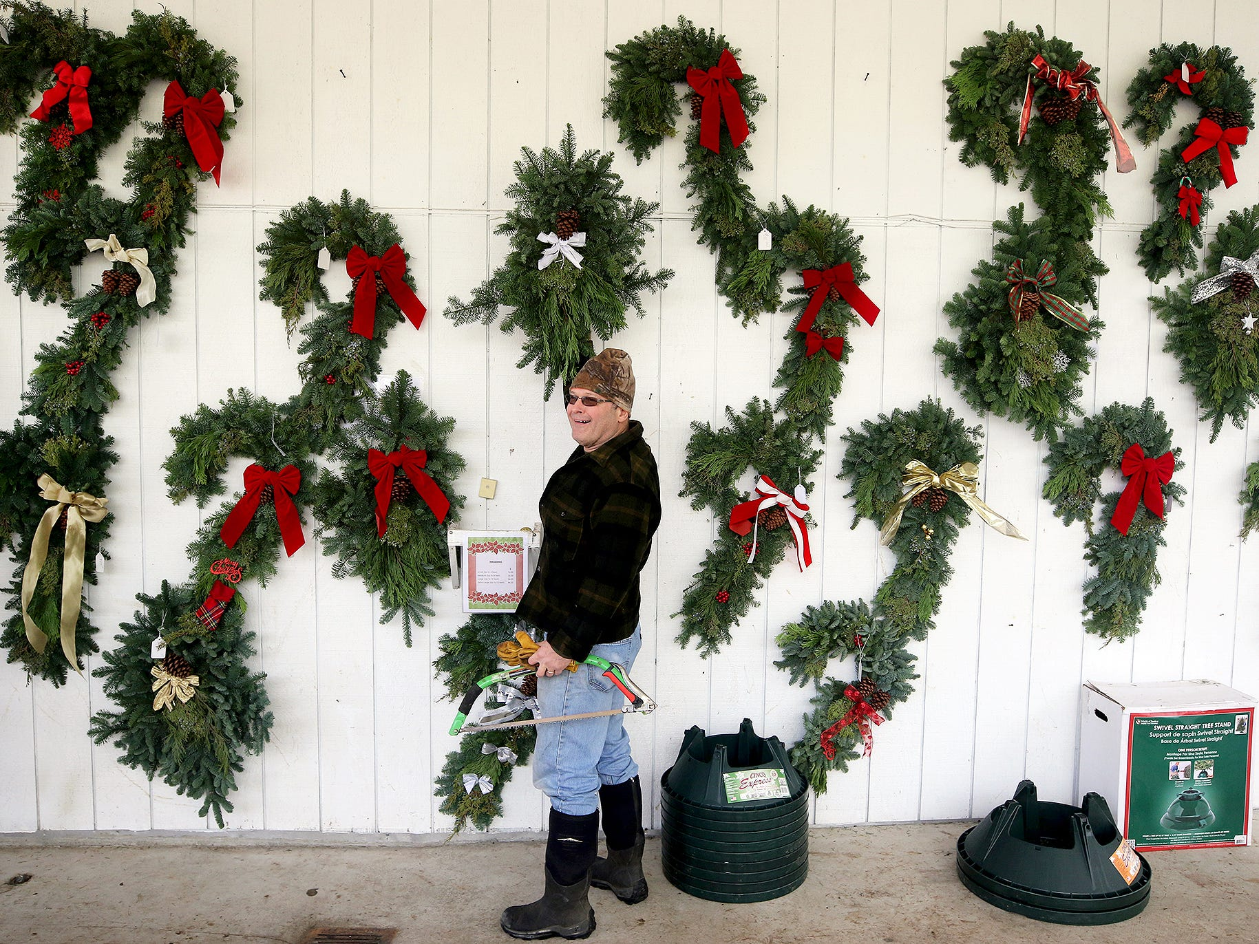 D. James Little of the All Creatures Animal Hospital in Gorst chooses hand made wreathes at the Bacon's Christmas Tree Farm on West Belfair Valley Rd, between Bremerton and Belfair on Monday, December, 10, 2018. He was getting the wreaths for his office Christmas party and to send some to family back east. The tree farm is closing early this year as Monday was the last day.