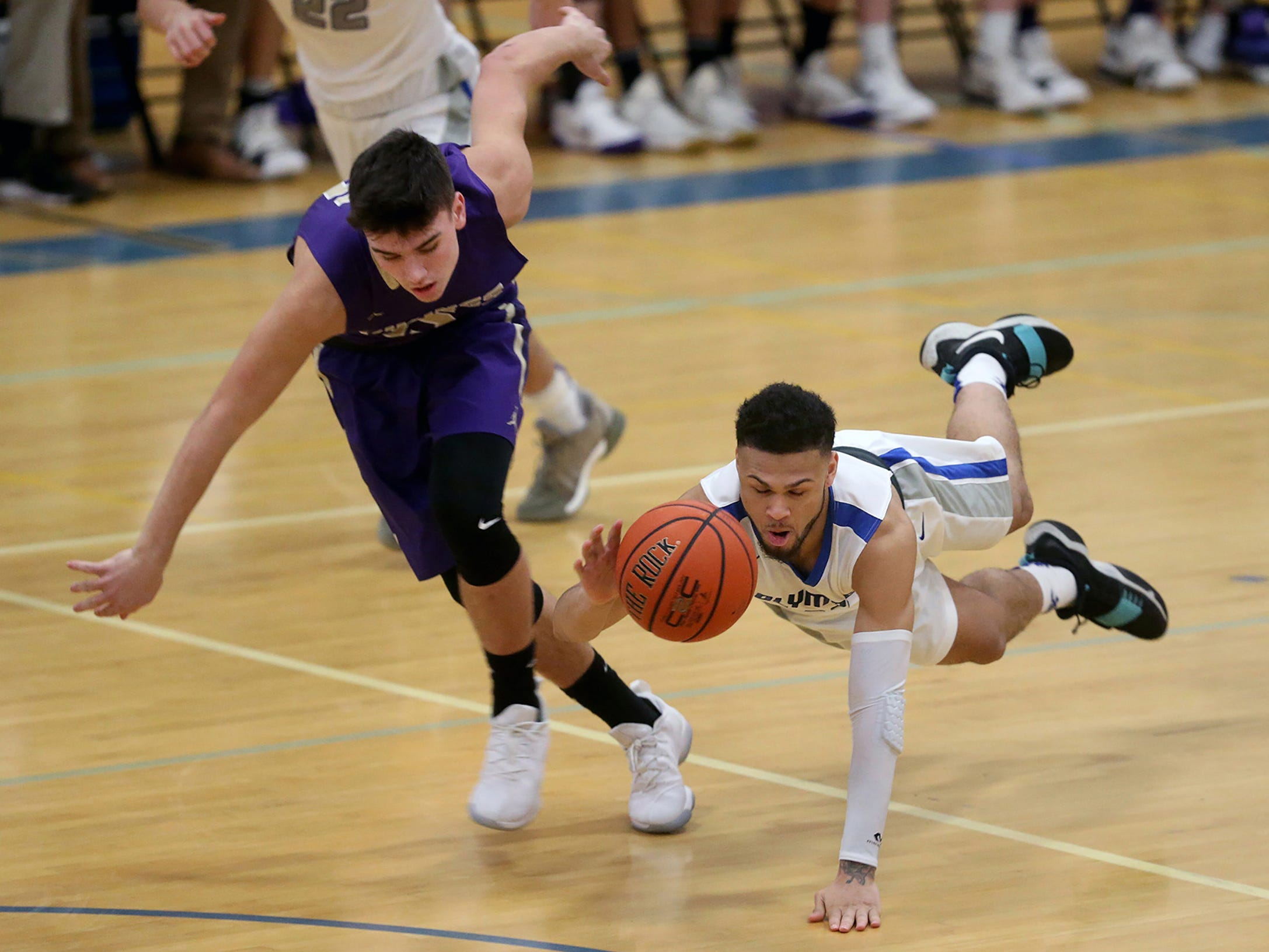 Olympic boys basketball player Jaiden Mosley dives for a loose ball as North Kitsap player Ryan Hecker goes for it Friday Jan, 12, 2017 at Olympic.