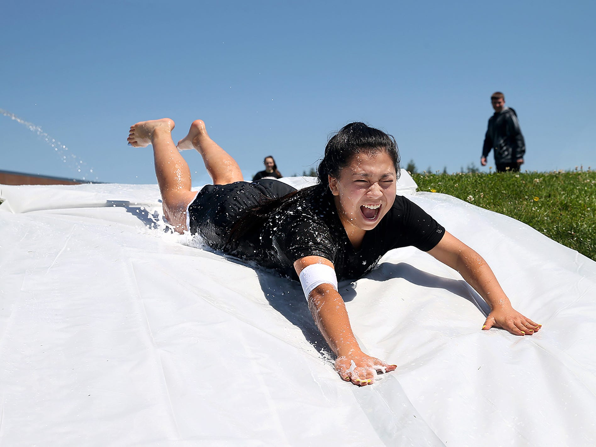 Ridgetop Middle School eighth grade student Meghan Landon, 14, goes down the slip-and-slide at the field day event Tuesday June 19, 2018.. Wednesday is the last day of school. She said it's her first every time going down a slide.