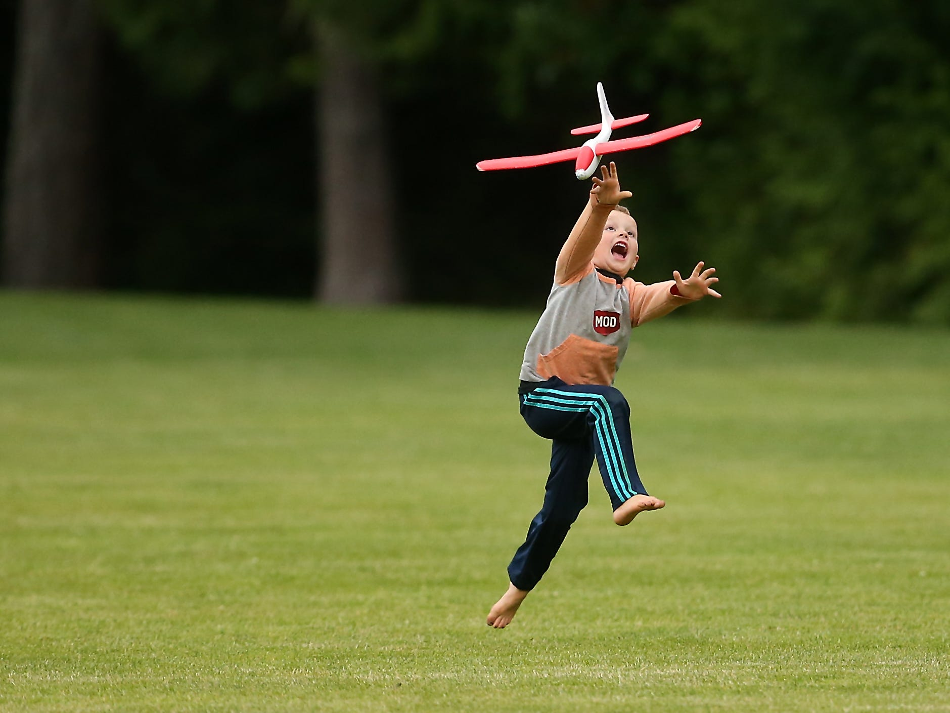 Raleigh Danger Anderson, 5, launches his glider into the air with a running leap while he and brother Stryker, 8, fly gliders with their grandmother Janet at Gordon Field in Bremerton, Washington on Wednesday, June 27, 2018.
