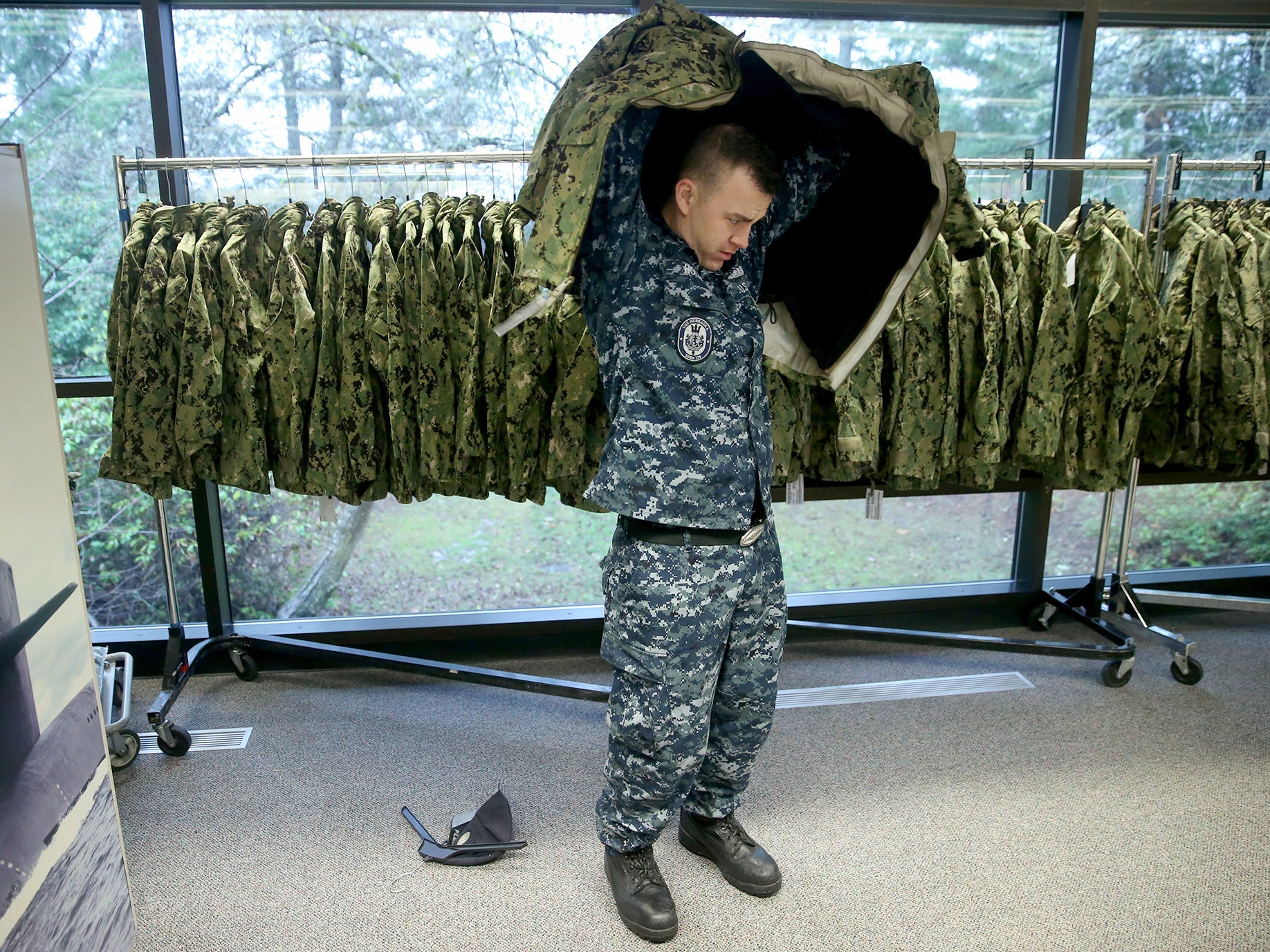 U.S. Navy sailor TM 2 Mason Holmes tries on a new green camouflage coat at the NEX on Naval Base Kitsap . Bangor. The Navy is changing from the blue camouflage to the green.