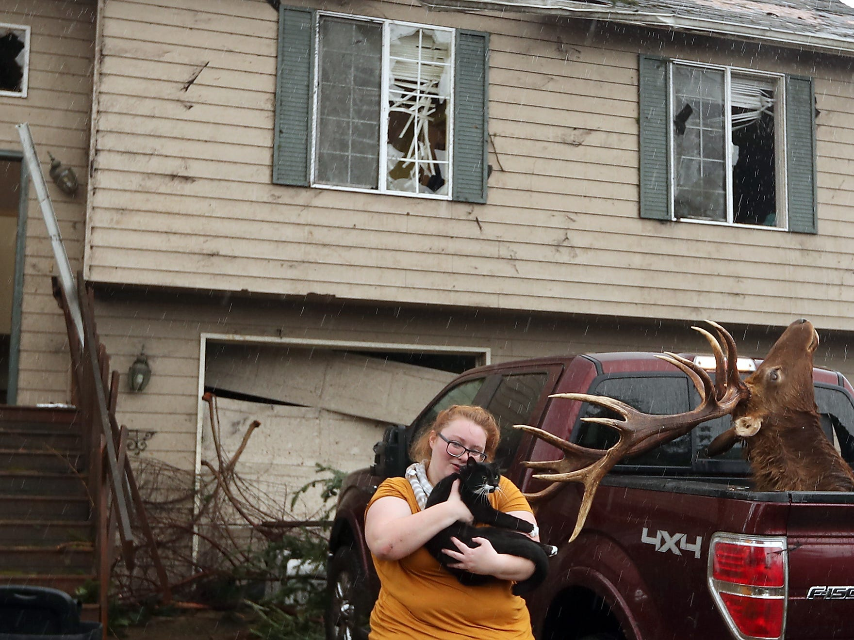 Morgan Crain hurries through the rain as she snuggles her cat Loki after finding him scared and hiding under one of the beds of her family's heavily damaged home in Port Orchard, Washington  on Wednesday, December 19, 2018. The Crain's found two of their three cats missing after and EF2 tornado hit on Tuesday. (AP Photo / Meegan M. Reid, Kitsap Sun)