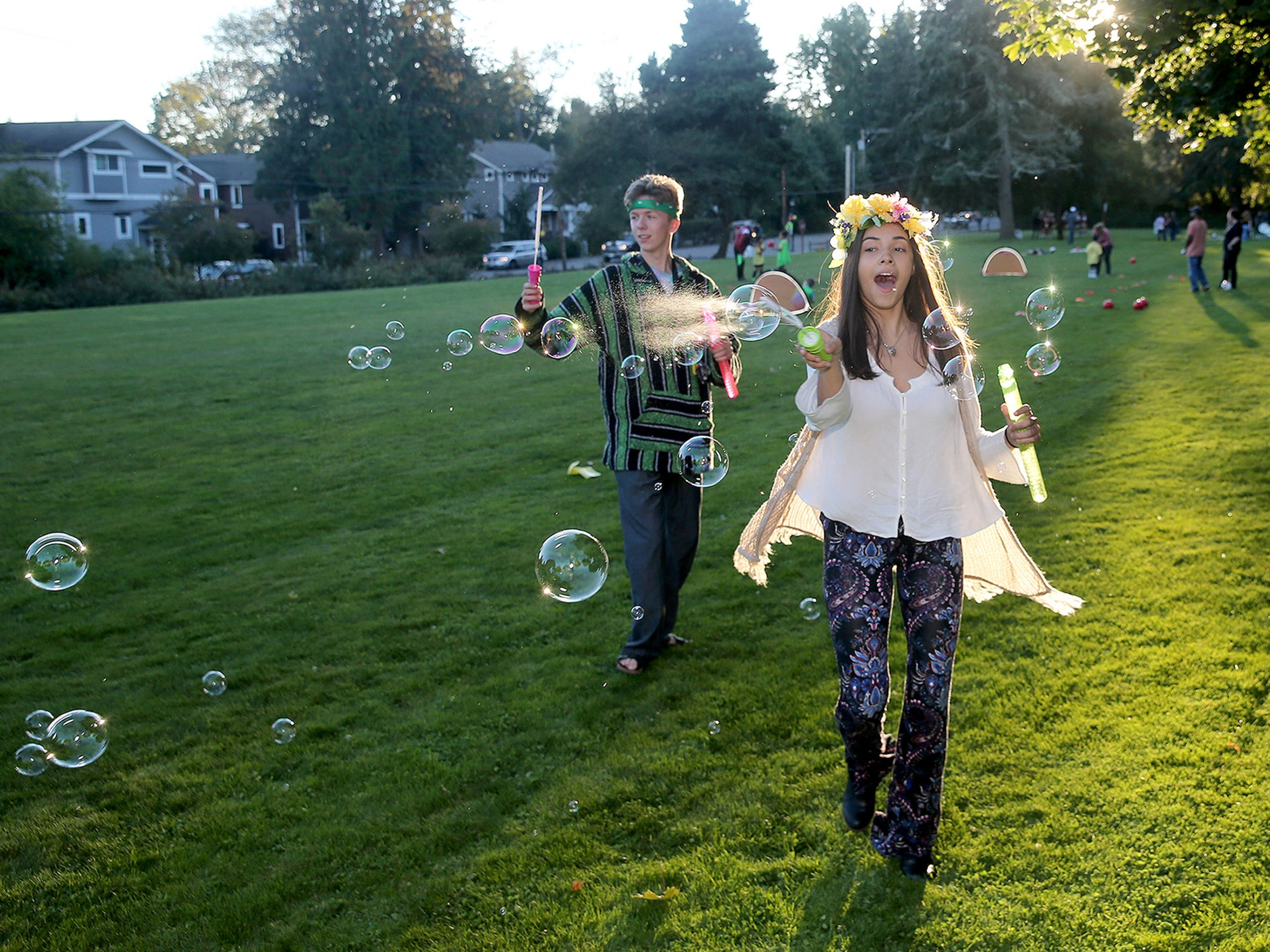 Kingston High School junior Justice Correa-West, 16, dressed as a 1960's hippy makes bubbles before the start at the annual Kingston High School Homecoming parade which had a theme of different decades floats for the freshman through senior classes  started at the Village Green Park to Mike Wallace Park in Kingston on Wednesday, September 26, 2018.