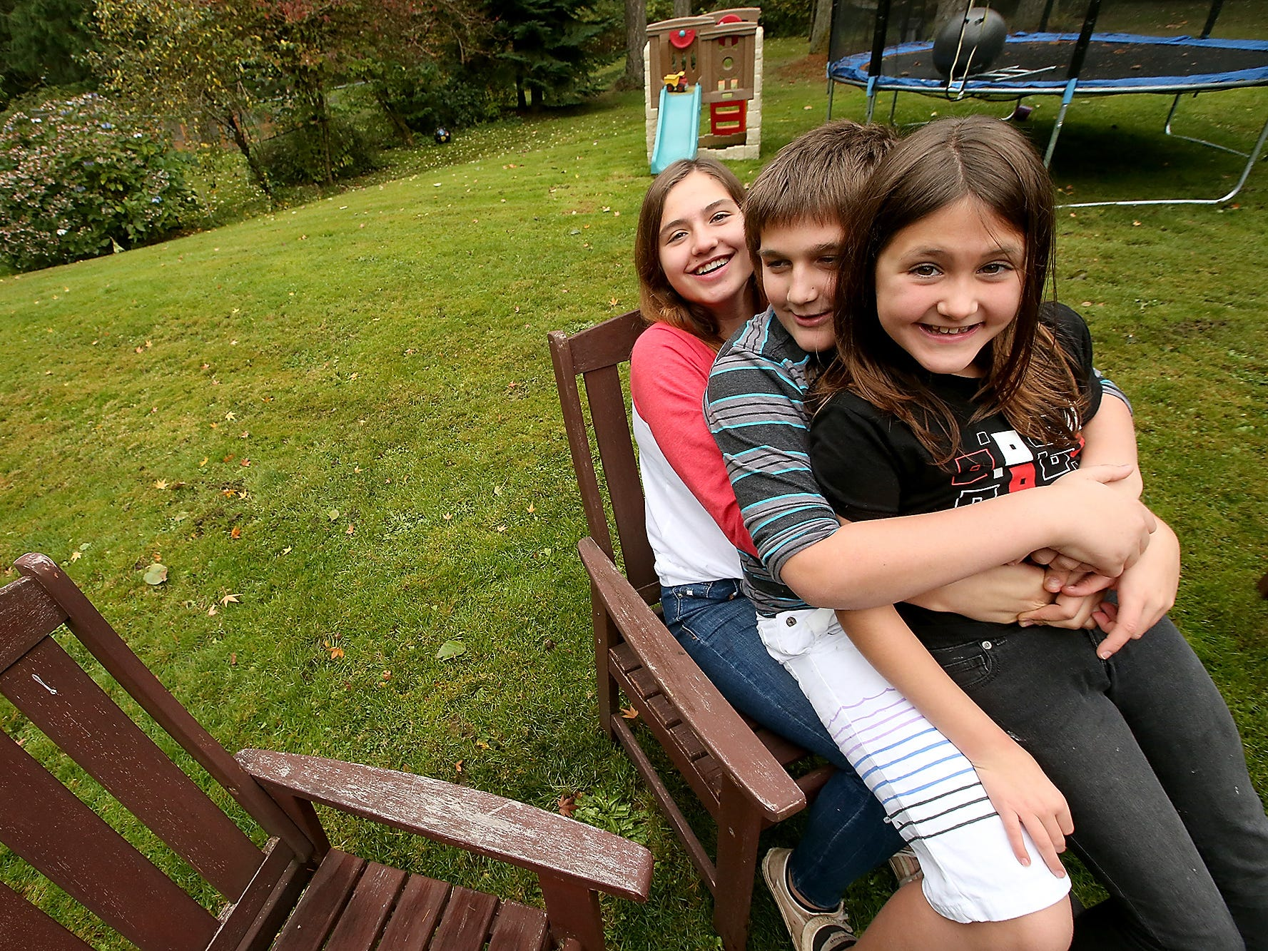 The Alcover siblings (back to front) Kylie, 15, Gavin, 11, and Phoenix, 9, jokingly sit in one chair for a portrait on Wednesday, November 14, 2018. The close-knit siblings from California lost their home in the Paradise fire and are staying with family friends Amber and Douglas Shaw in Suquamish, Washington while their parents work things out in California.