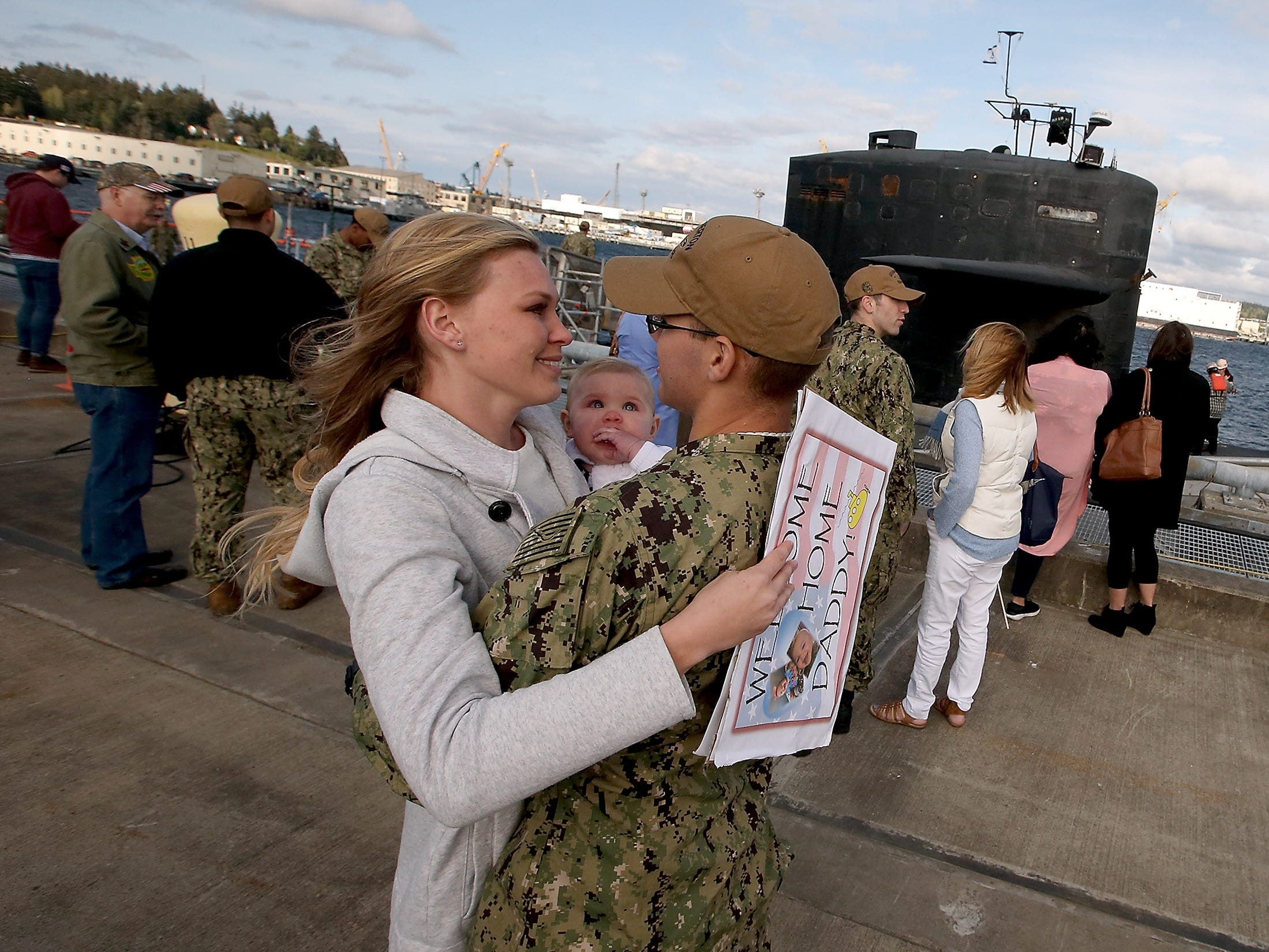 Breanna Squires embraces her husband Harley while 8-month-old daughter Olivia looks on after Harley disembarked the USS Bremerton at Naval Base Kitsap-Bremerton on Friday, April 27, 2018. The submarine is scheduled to begin the inactivation and decommissioning process at the Puget Sound Naval Shipyard in July