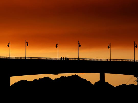 The sky turns orange at the end of Saturday as pedestrians walk across the Manette Bridge from Shore Drive in Manette.