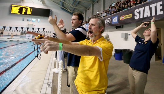 Bainbridge swim coach and athletic director Kaycee Taylor reacts to swimmer Jude Wenker's first place finish in the 100 Yard Freestyle during the 3A Boys Swim/Dive Championships at the King County Aquatics Center in Federal Way, Washington on Saturday, Feb. 17, 2018.