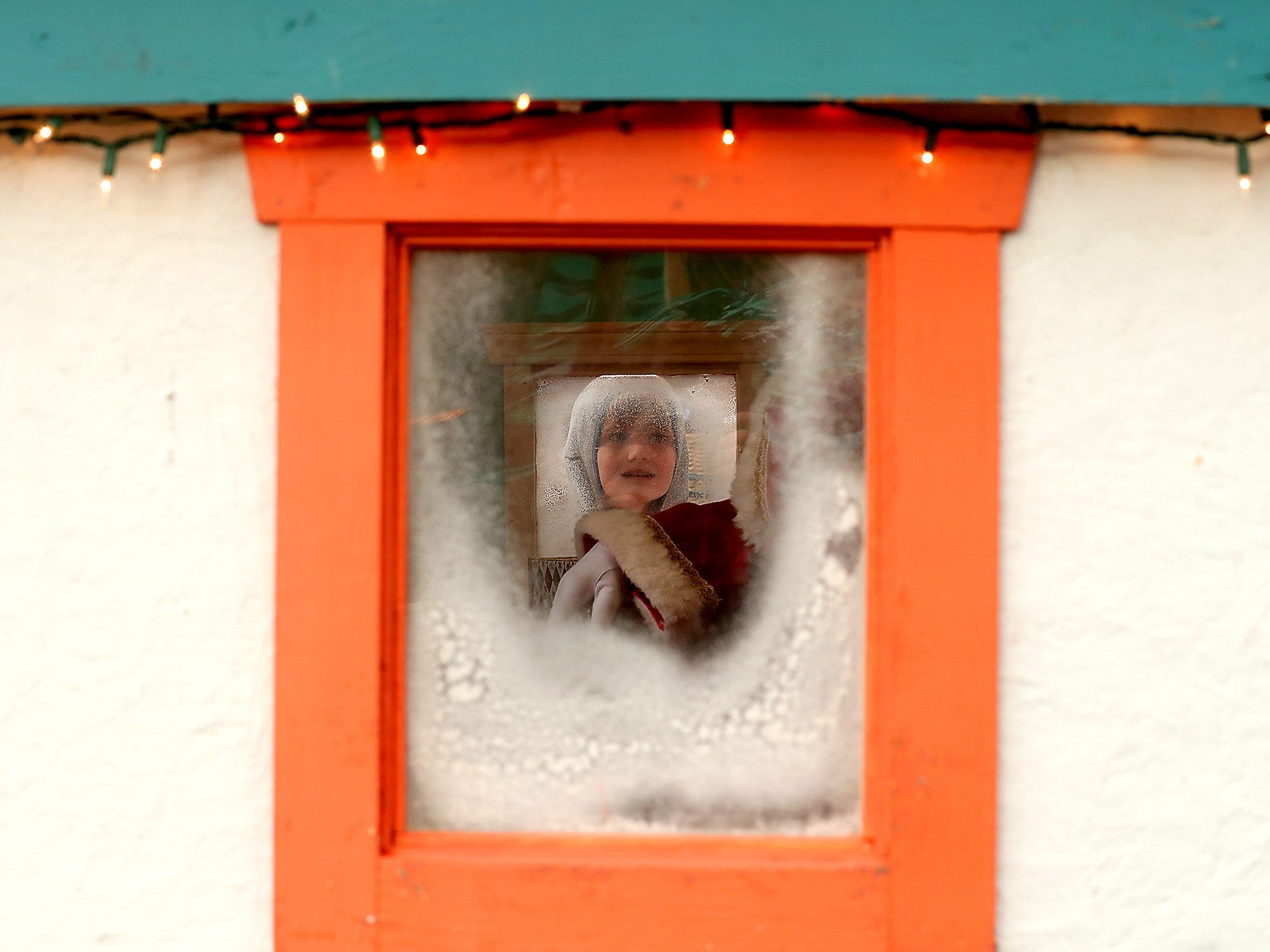 Clark Rasmussen, 6, peeks into the faux-frosty window of Nordic Father Christmas' hut in downtown Poulsbo, Washington on Friday, November 23, 2018. Clark was too shy to talk to Nordic Father Christmas, played by Danny Fritts, so he stuck with peeking into the windows of the small hut as other kids had their photos taken. Those outgoing enough to visit Nordic Father Christmas in his house can head to downtown Poulsbo 11 to 3 on Saturdays and 12 to 3 on Sundays and donations benefit Fishline.