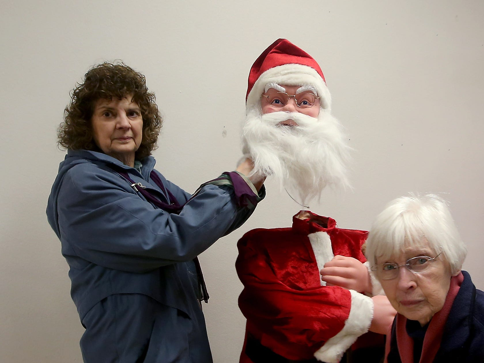 Volunteer Marghi Zarinelli (left) and Kathy Shubert attach the head of a motorized Santa as they prepare the Christmas decorations section for the annual Kitsap Rotary Auction and Garage Sale at the Kitsap Sun Pavilion on Thursday, April 12, 2018.