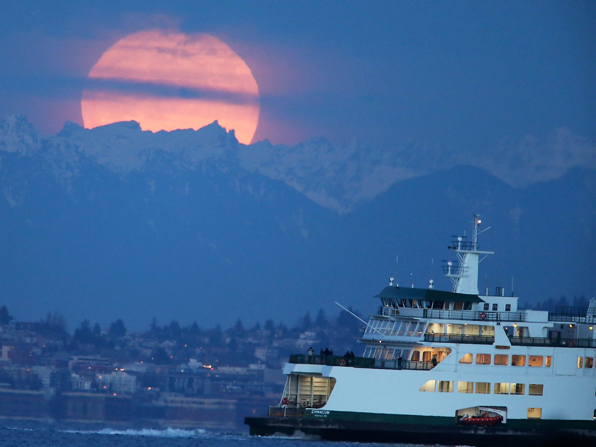 The supermoon rises behind the clouds and the Cascade Mountains as the Washington State Ferry Chimacum heads to Seattle from Bremerton, on Monday, Jan. 1, 2018 in Manchester, Washington.