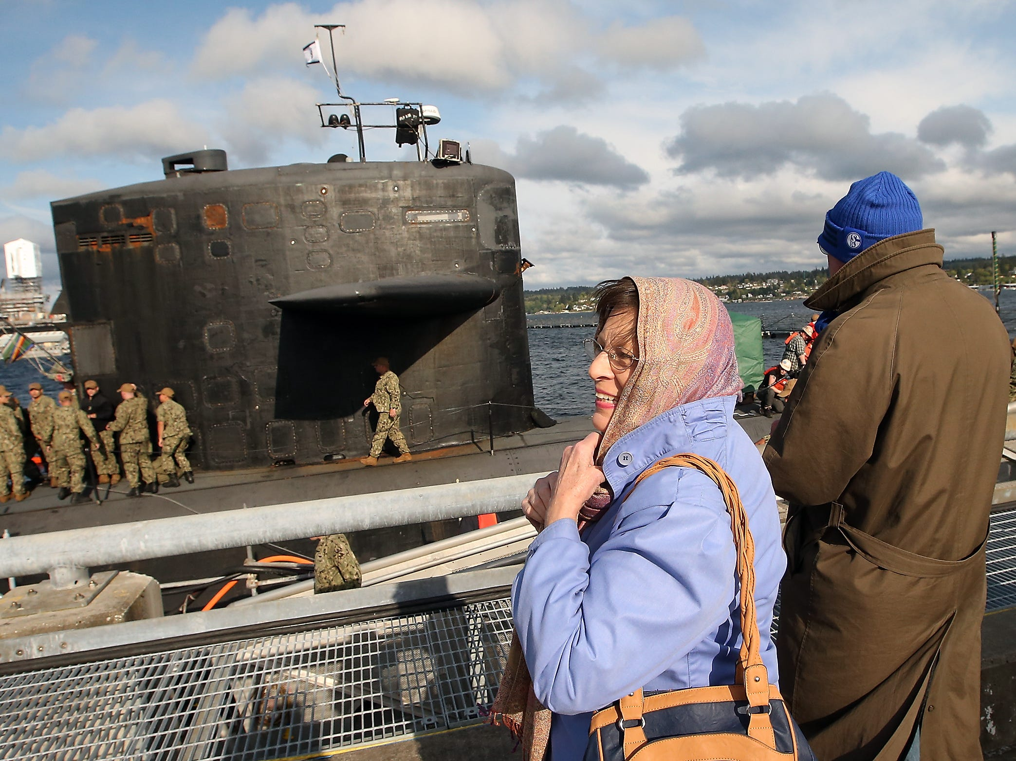 Cynthia Karottki tightens her head scarf against the wind as she and husband Hartmut (right) watch the USS Bremerton for their sailor son Christoph to disembark the submarine at Naval Base Kitsap-Bremerton on Friday, April 27, 2018. The Karottki's traveled all the way from Massachusetts to see their son who was deployed aboard the USS Bremerton for it's last mission before its decommissioning at Puget Sound Naval Shipyard.