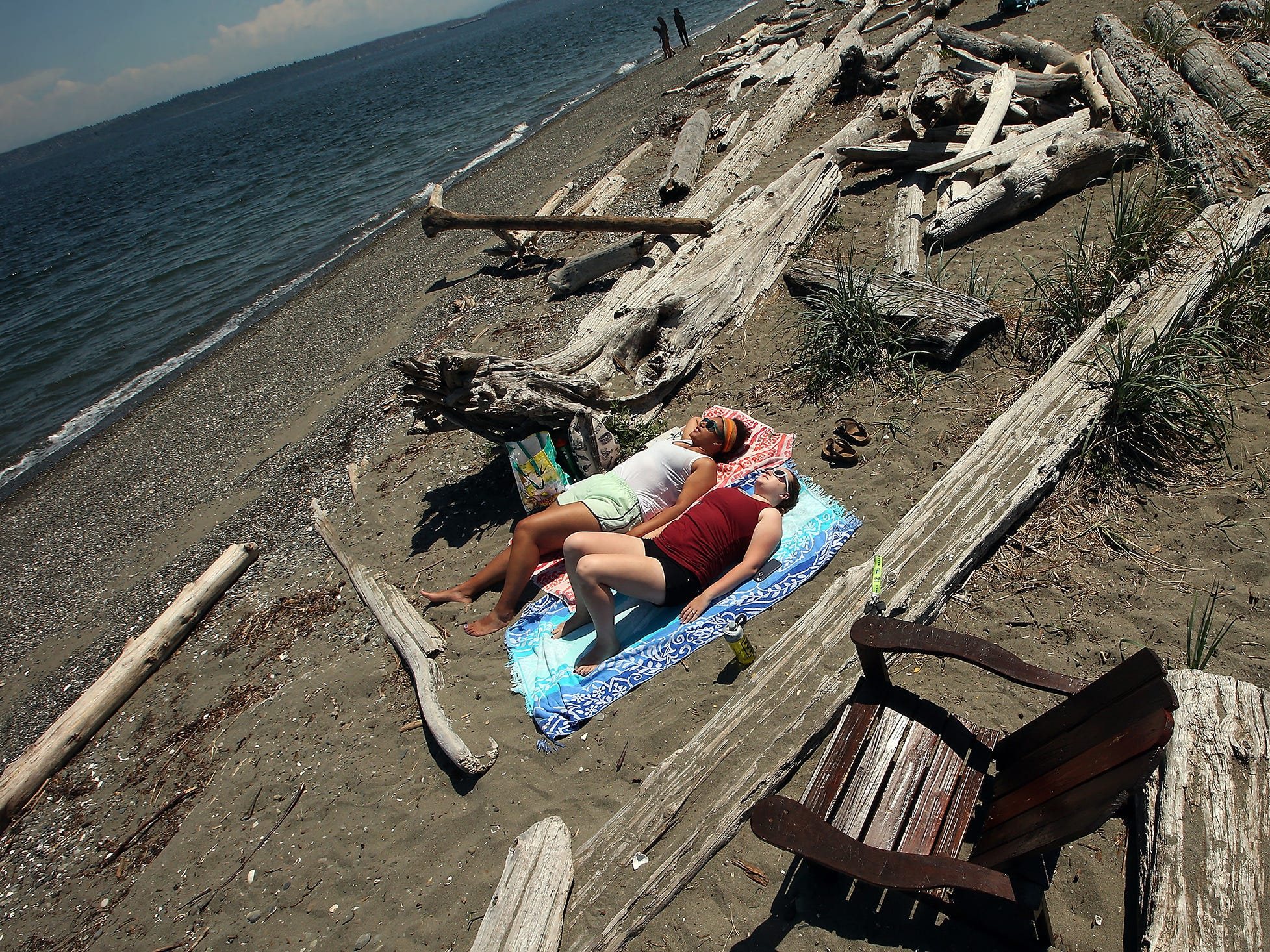 Friends Mikala Cummins, of Bainbridge Island, (front) and Shawna Nelson, of Ketchikan Alaska, sunbathe among the driftwood logs on the beach at Fay Bainbridge Park on Bainbridge Island on Wednesday, May 23, 2018.