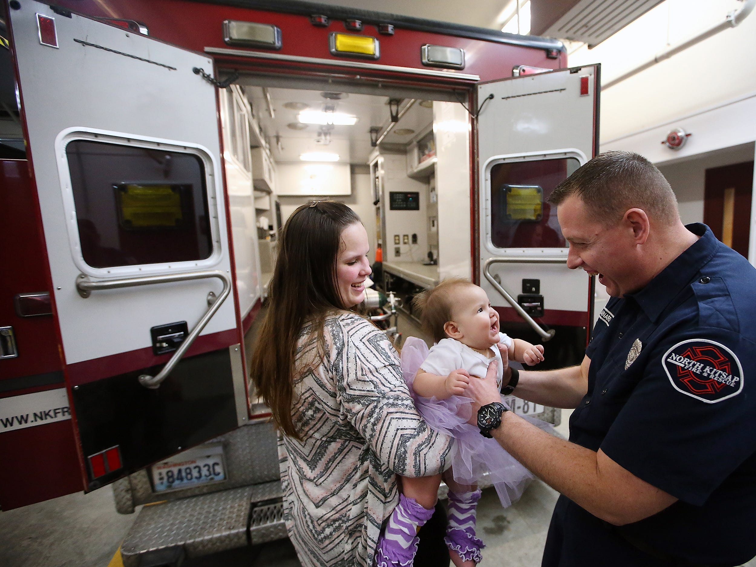 North Kitsap Fire and Rescue firefighter/paramedic Craig Barnard takes one-year-old Eleanor from her mom Lakeisha Rogers while they stand behind Medic 81 at  North Kitsap Fire & Rescue Headquarters Station 81 in Kingston, Washington on Tuesday, Feb. 6, 2018. Barnard delivered Eleanor a year earlier in the back of the medic unit, just before the intersection of SR 307 and SR 305, while transporting them from their Little Boston home to the hospital. The Rogers family stopped by the station to celebrate Eleanor's first birthday with the first responders who were there.