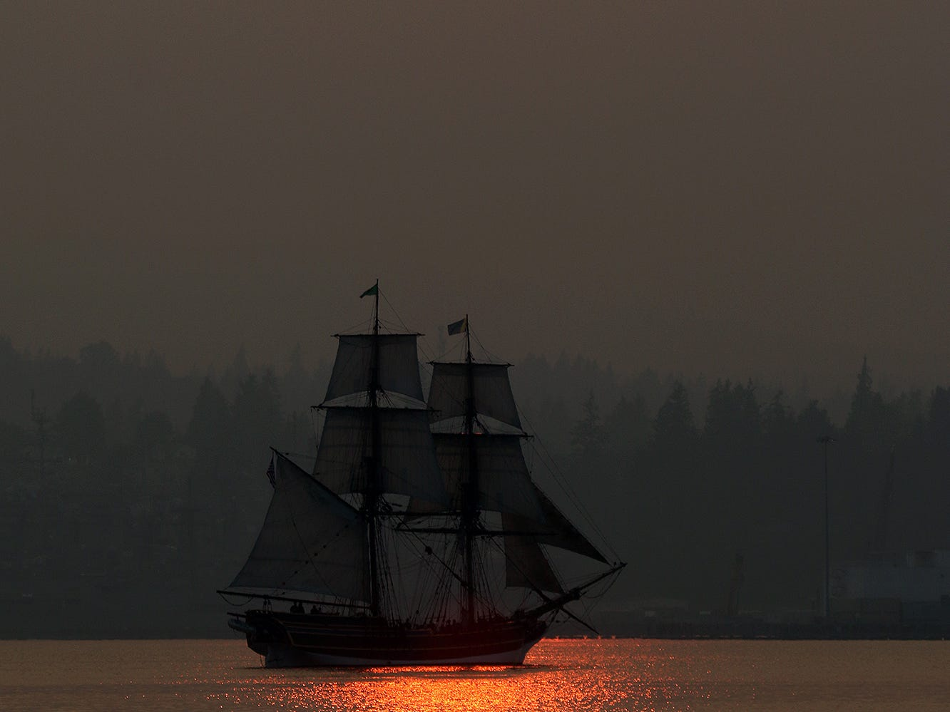 The tall ship Lady Washington sails off Port Orchard through the haze at sunset on Tuesday August 14, 2018.