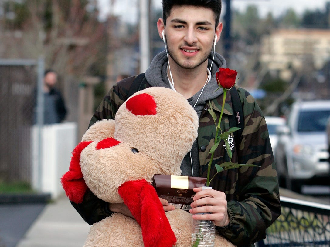 Ruben Godinez of Bremerton carries gifts to give to his girlfriend for Valentine's Day as he walks to the Port Orchard ferry along Pacific Ave. and ninth street in Bremerton. He said he has gotten plenty of complements as he walked.
