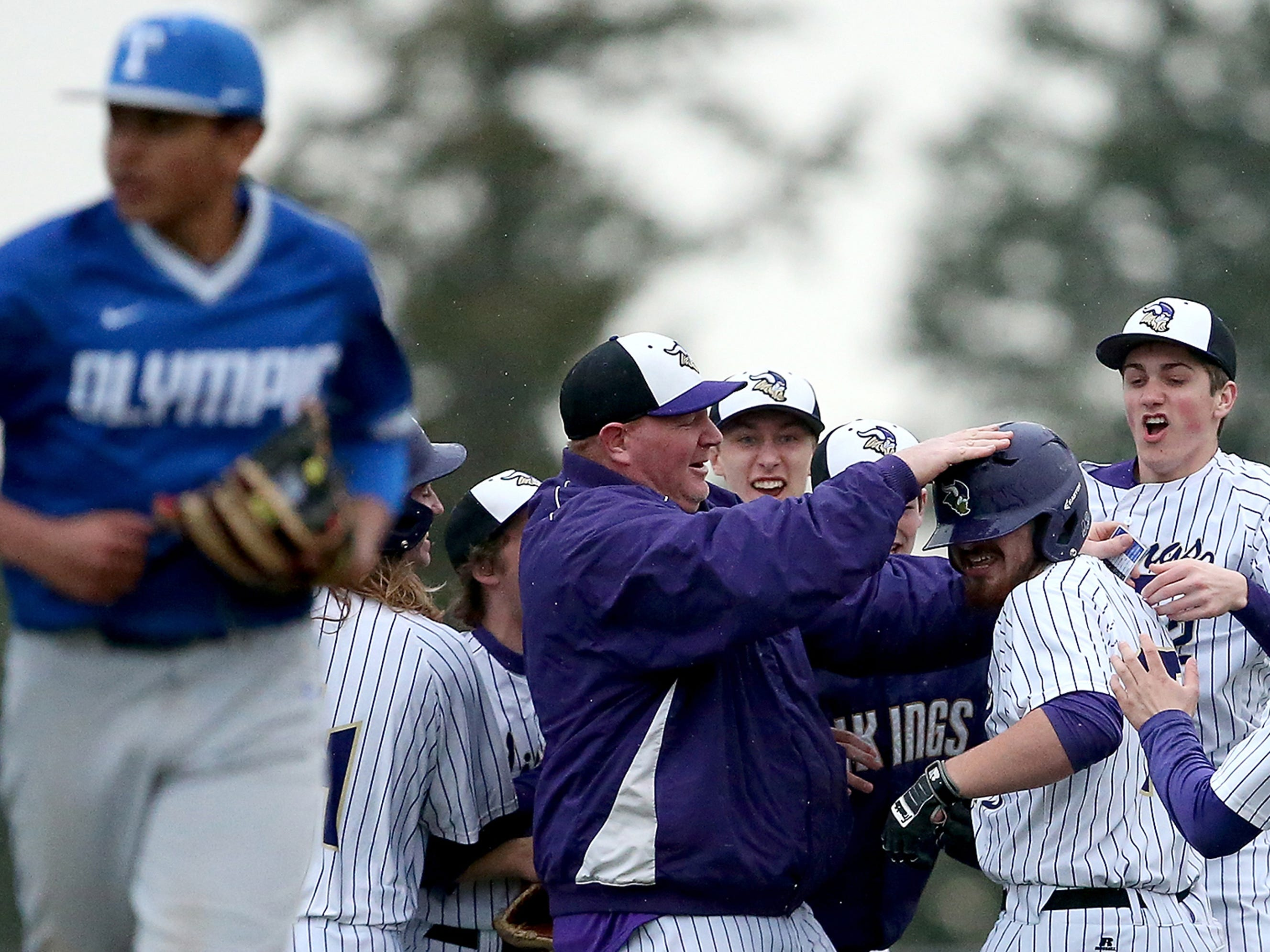 North Kitsap coach Jeff Weible and his team congratulate Tucker Gowin on his game winning hit in the seventh inning against Olympic in Poulsbo, Washington on Wednesday, March 21, 2018.