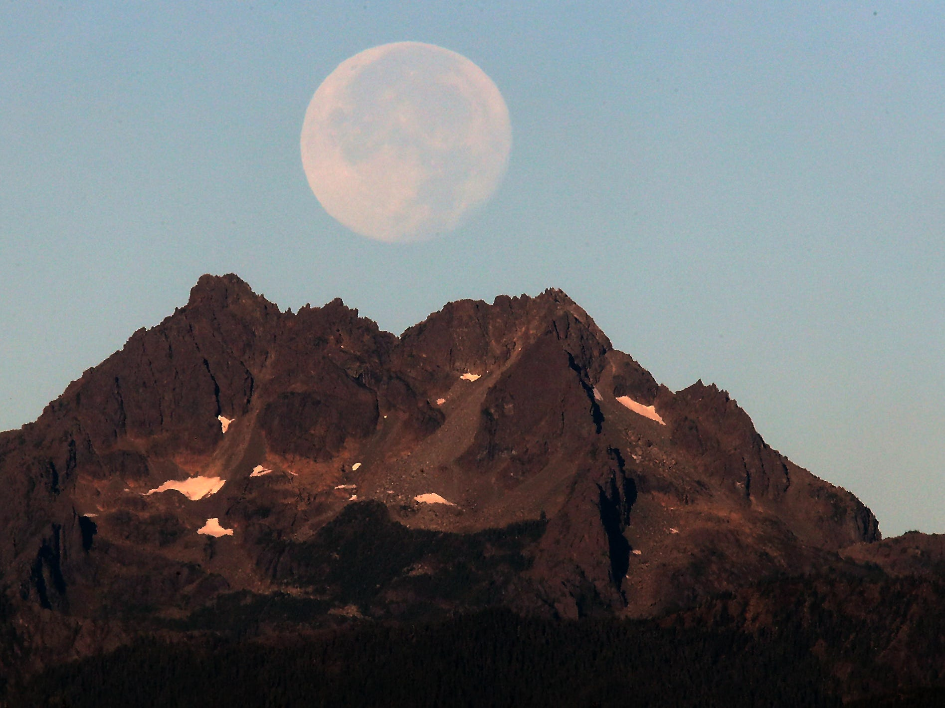 The moon sets above the Brothers of the Olympic Mountain Range as viewed from Silverdale, Washington on Wednesday, September 26, 2018.