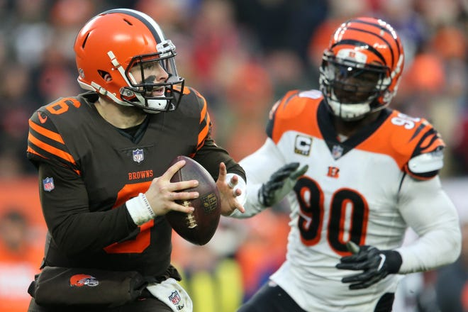 Cleveland Browns quarterback Baker Mayfield (6) rolls out of the pocket as Cincinnati Bengals defensive end Michael Johnson (90) gives chase in the fourth quarter of a Week 16 NFL football game, Sunday, Dec. 23, 2018, at FirstEnergy Stadium in Cleveland. The Cleveland Browns won 26-18.