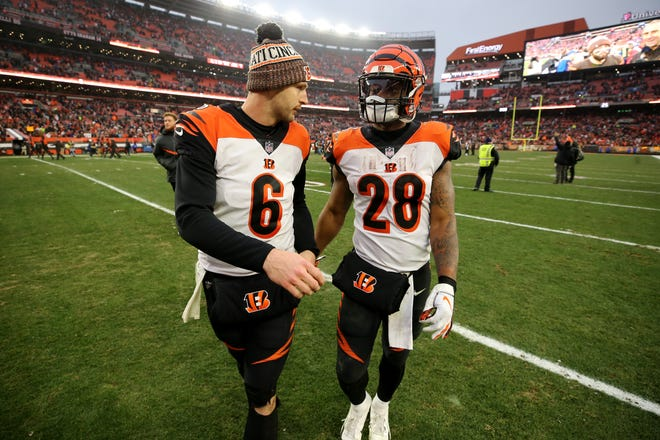 Cincinnati Bengals quarterback Jeff Driskel (6) and Cincinnati Bengals running back Joe Mixon (28) talk as they walk off the field after a Week 16 NFL football game against the Cleveland Browns, Sunday, Dec. 23, 2018, at FirstEnergy Stadium in Cleveland. The Cleveland Browns won 26-18.