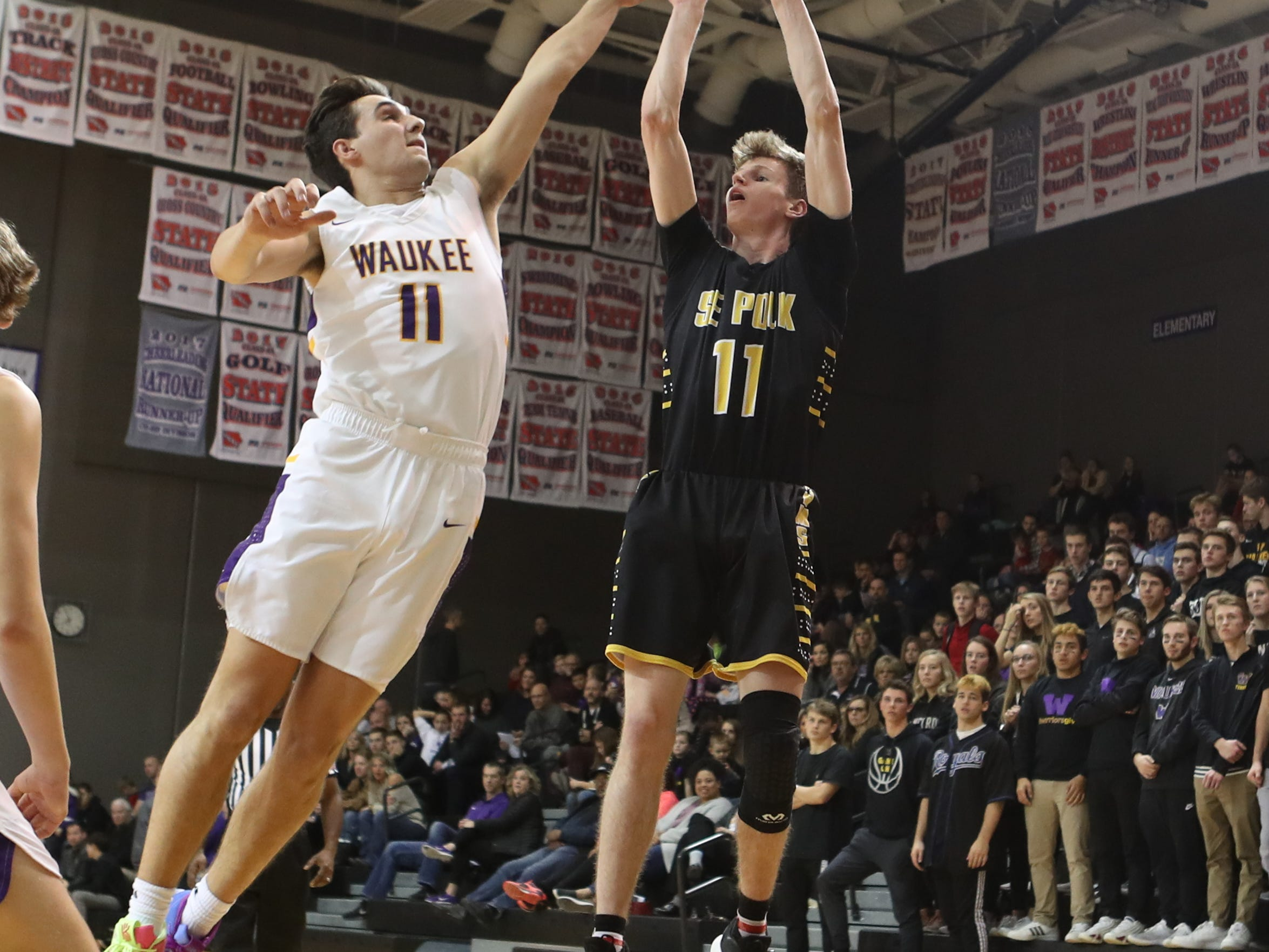 Dec 21, 2018; Waukee IA  USA; Southeast Polk Rams Sam Glenn (11) shoots over the top Waukee Warriors Noah Hart (11) at Waukee High School. Mandatory Credit: Reese Strickland-for the register