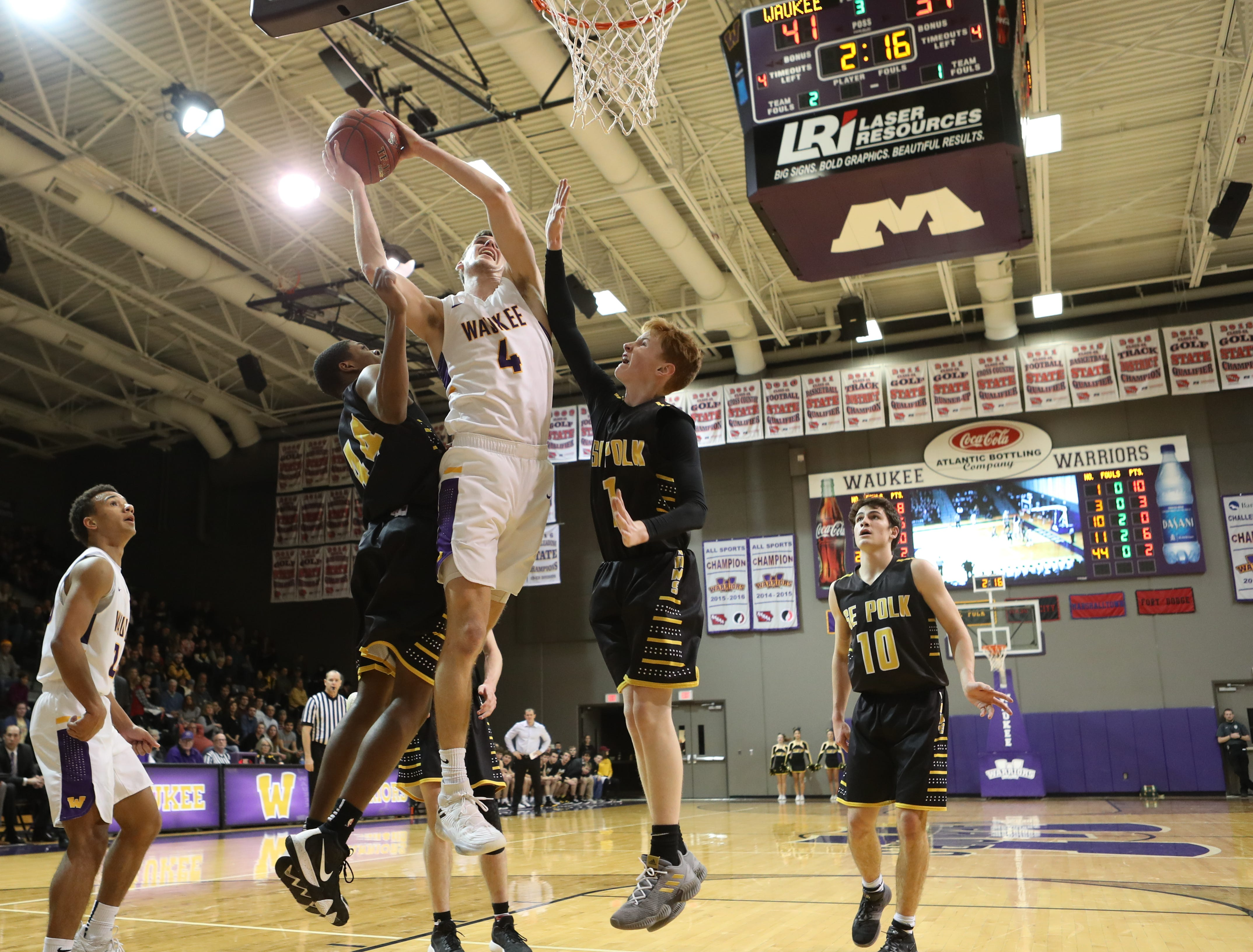 Dec 21, 2018; Waukee IA  USA;  Southeast Polk Rams Malichai Williams (44) and Southeast Polk Rams James Glenn (1) defends the shot of Waukee Warriors Dylan Jones (4) at Waukee High School. Mandatory Credit: Reese Strickland-for the register