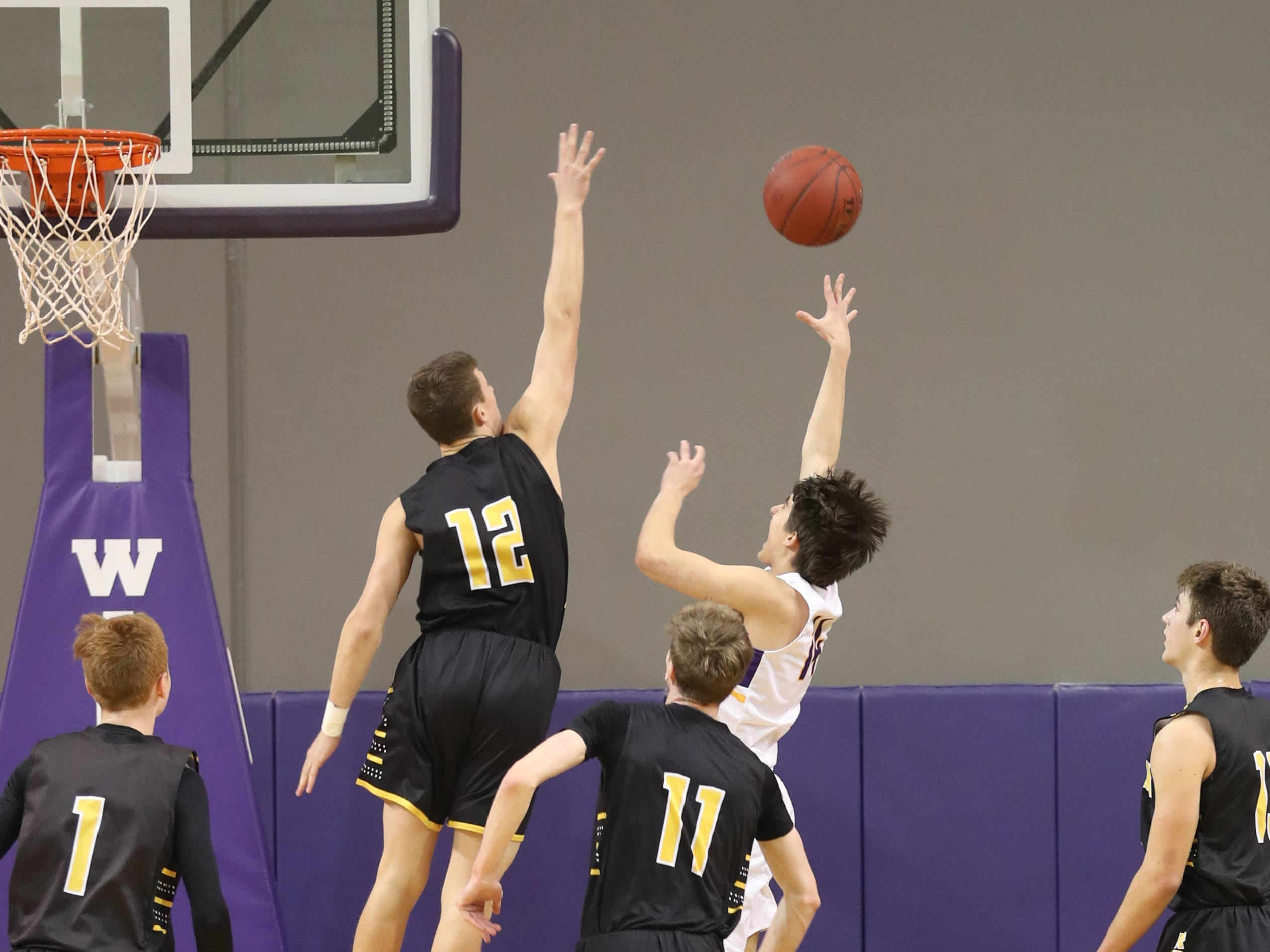 Dec 21, 2018; Waukee IA  USA; Waukee Warriors Dylan Jones (4) shoots over Southeast Polk Rams Fred Johnson (12) at Waukee High School. Mandatory Credit: Reese Strickland-for the register